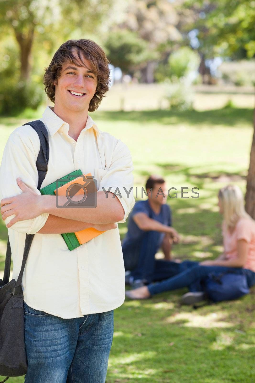 Smiling young man posing with textbook in a park with friends in background