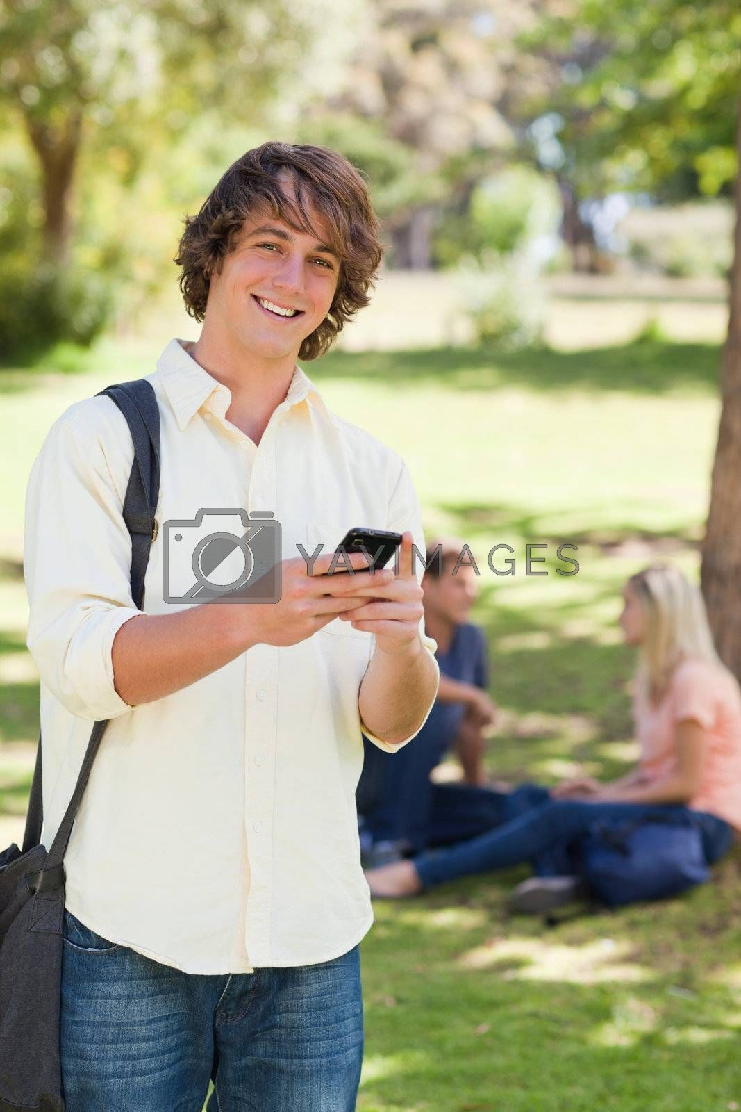 Portrait of a young man using a smartphone in a park with friends in background