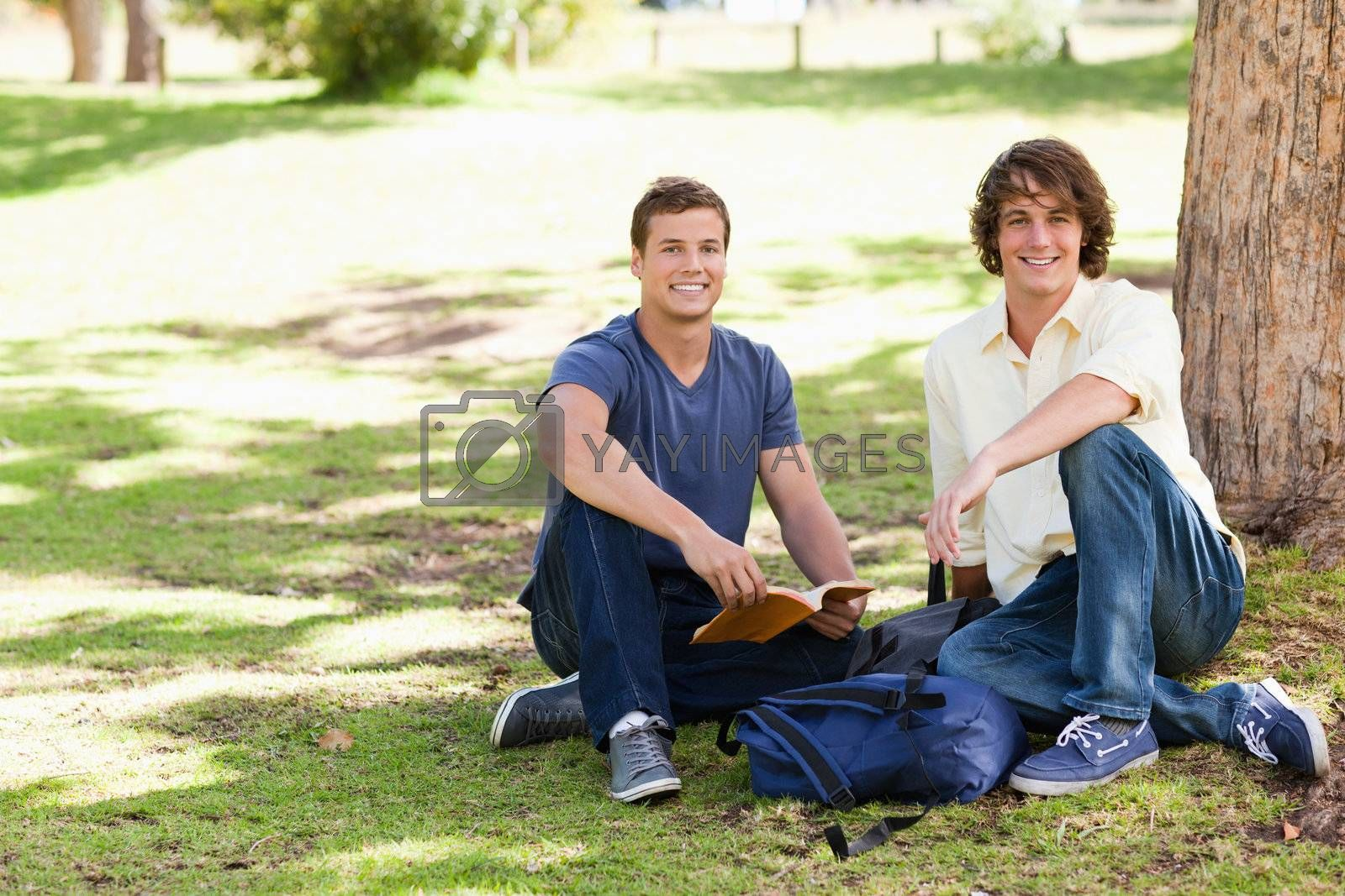 Two male students posing while studying in a park