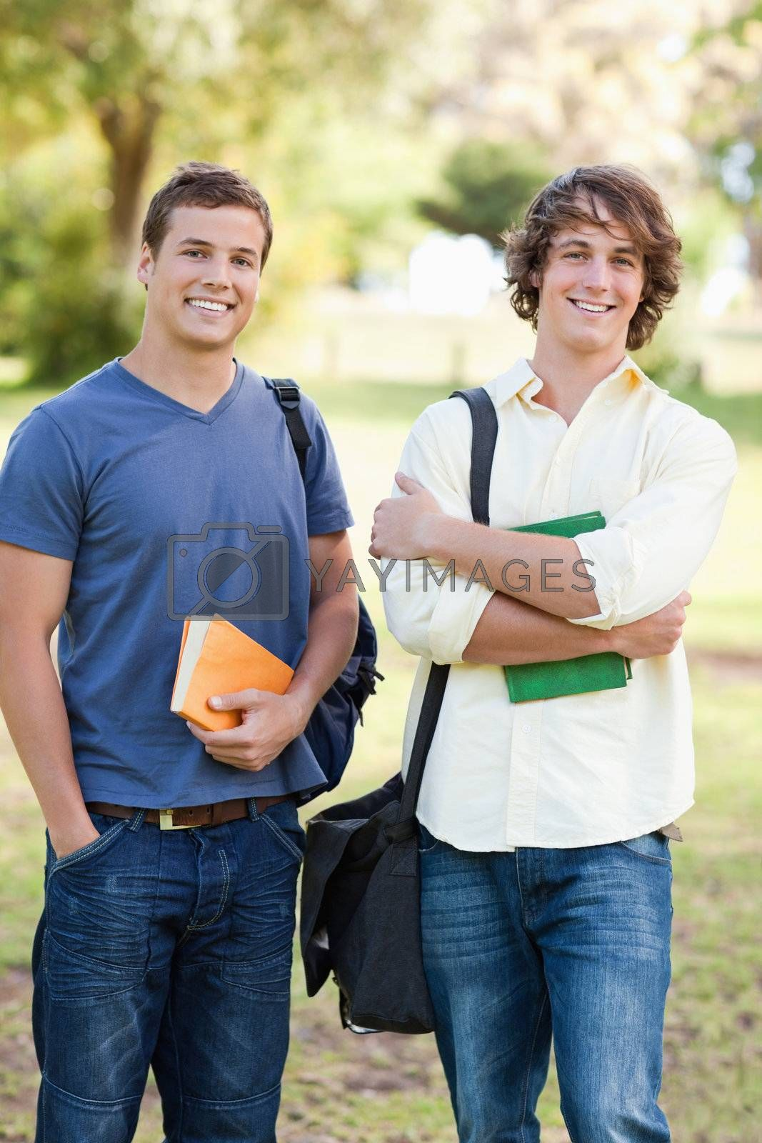 Portrait of two standing handsome students talking in a park