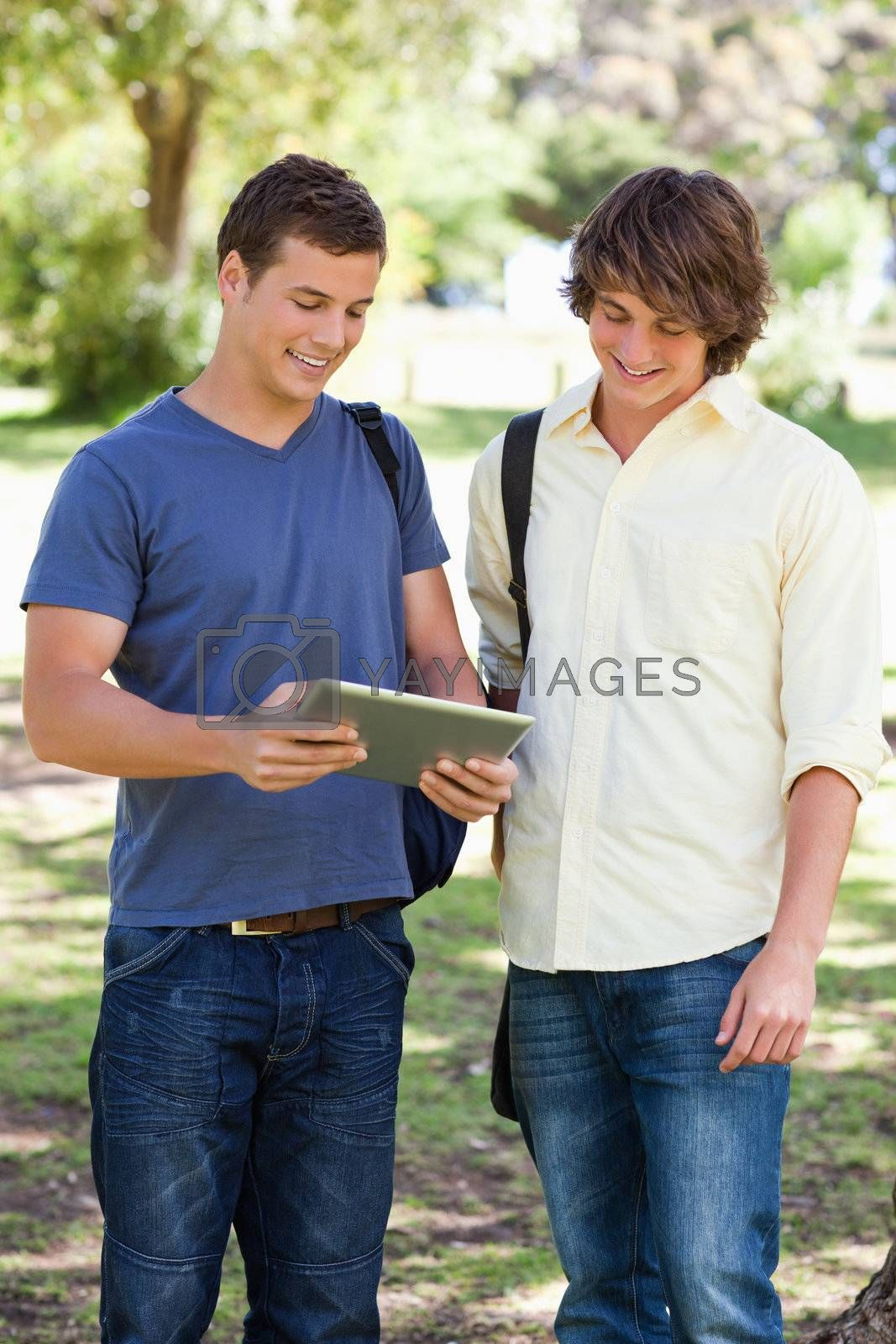 Two smiling male students with a touch pad in a park