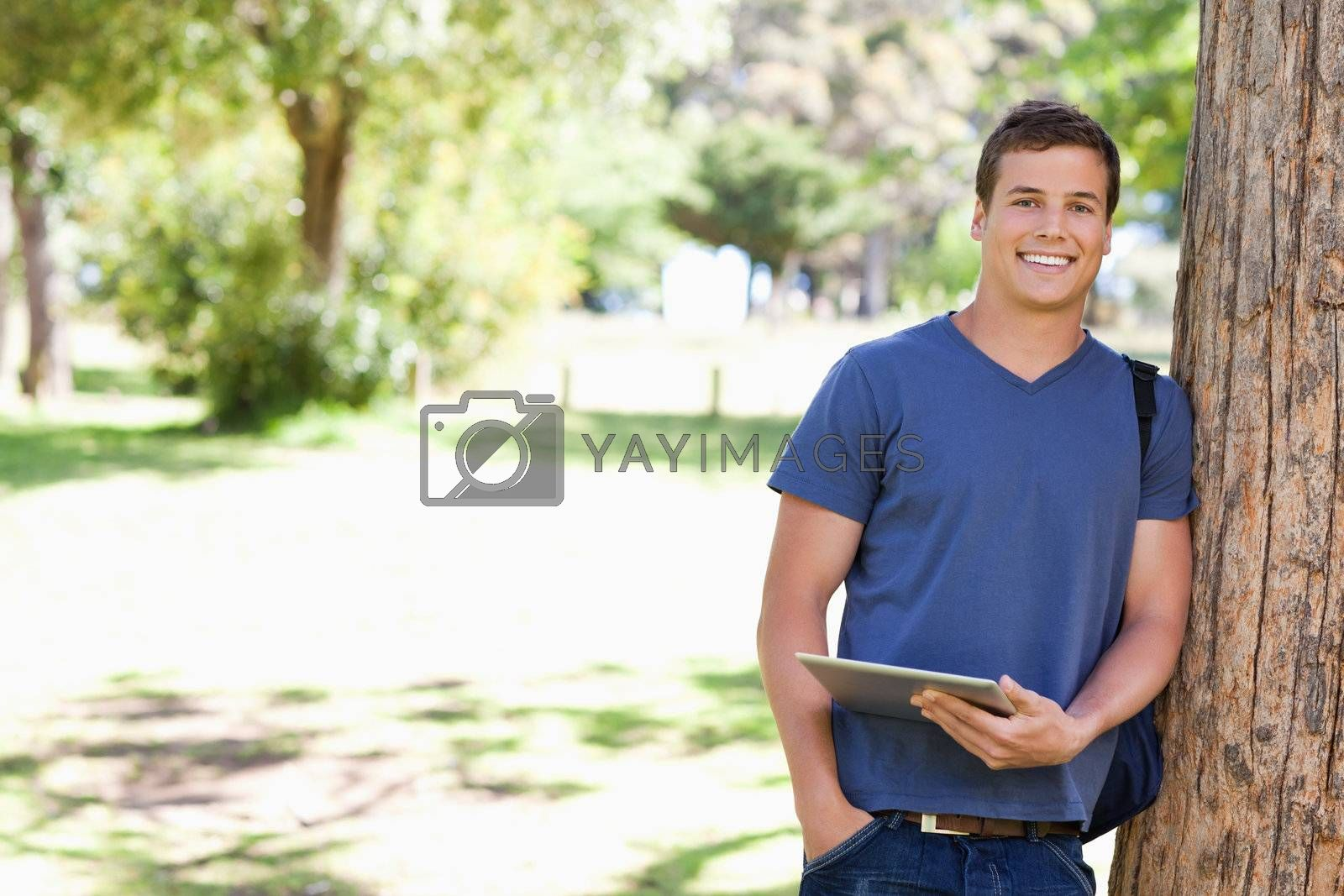 Portrait a student leaning against a tree with a touch pad in a park