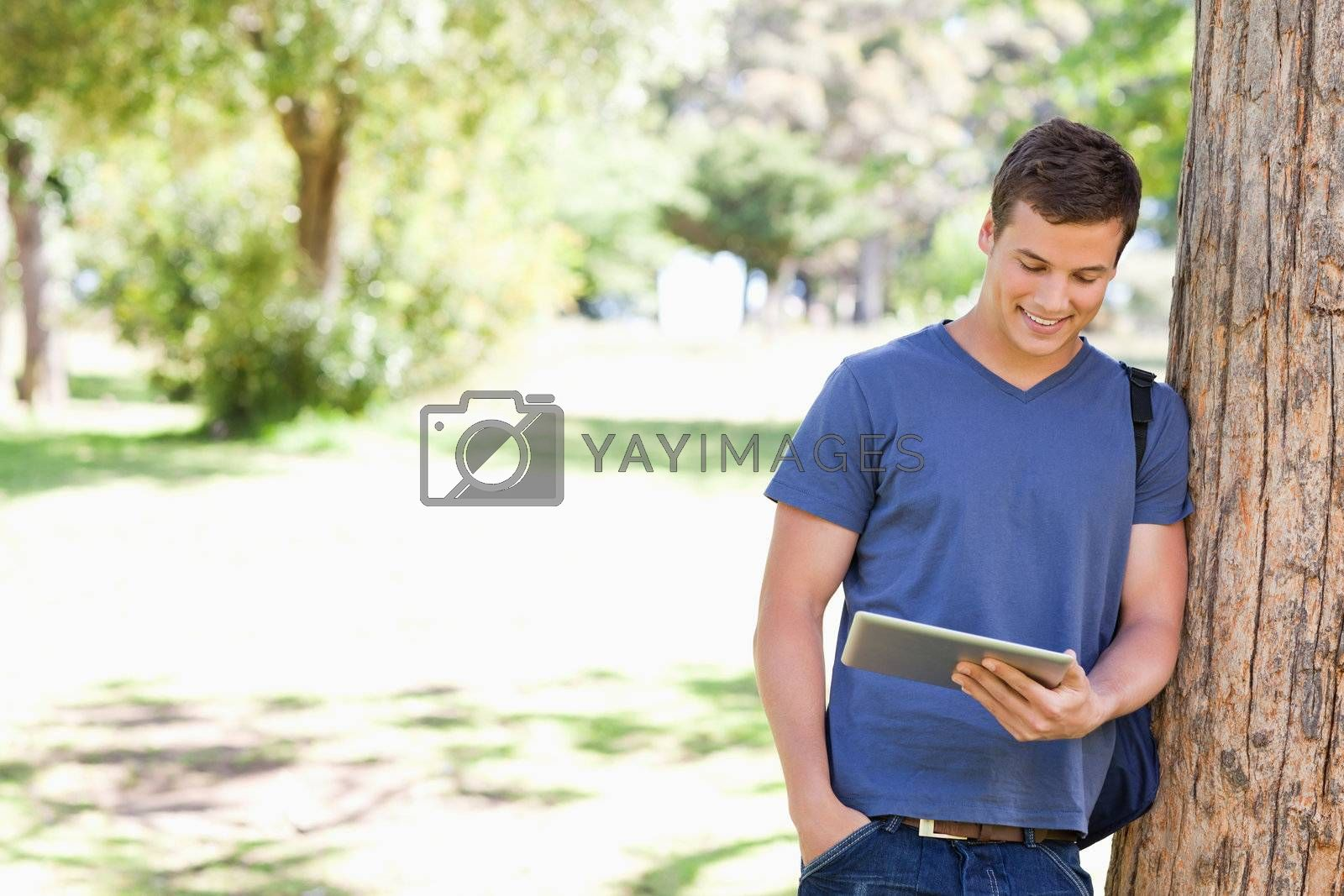 Student leaning against a tree with a touch pad in a park