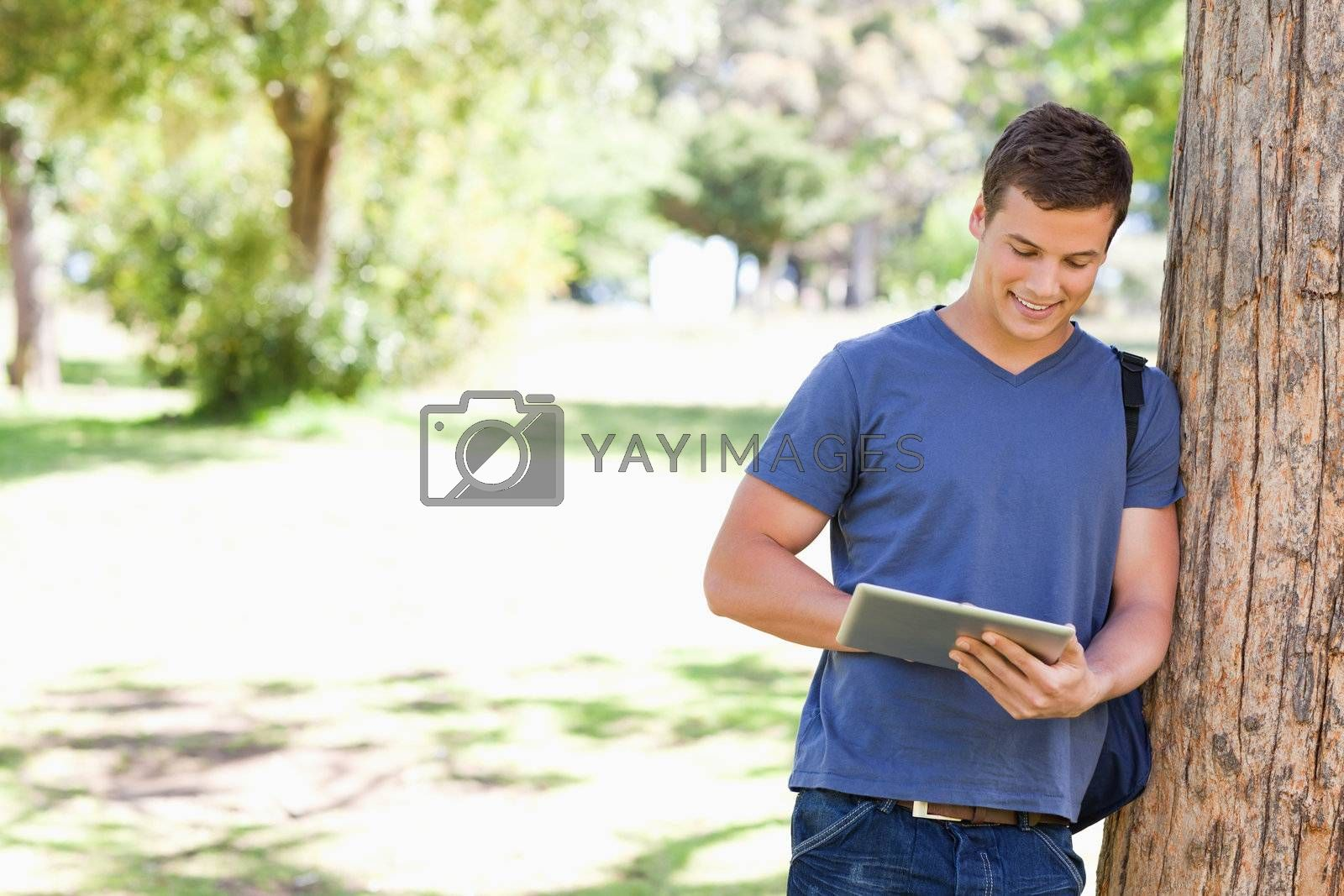 Student leaning against a tree while using a touch pad in a park