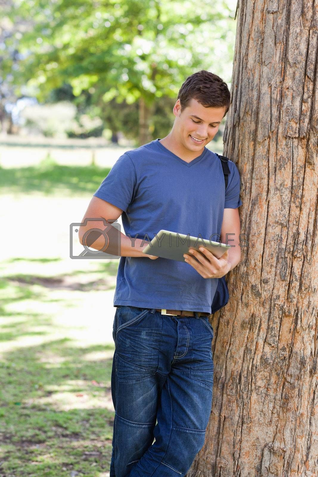 male student leaning against a tree while using a touch pad in a park