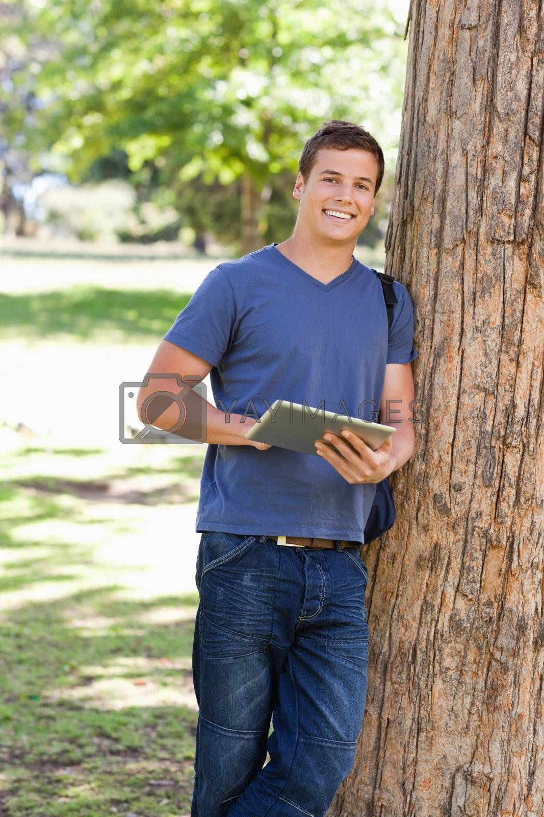Portrait of a student leaning against a tree while using a touch pad in a park