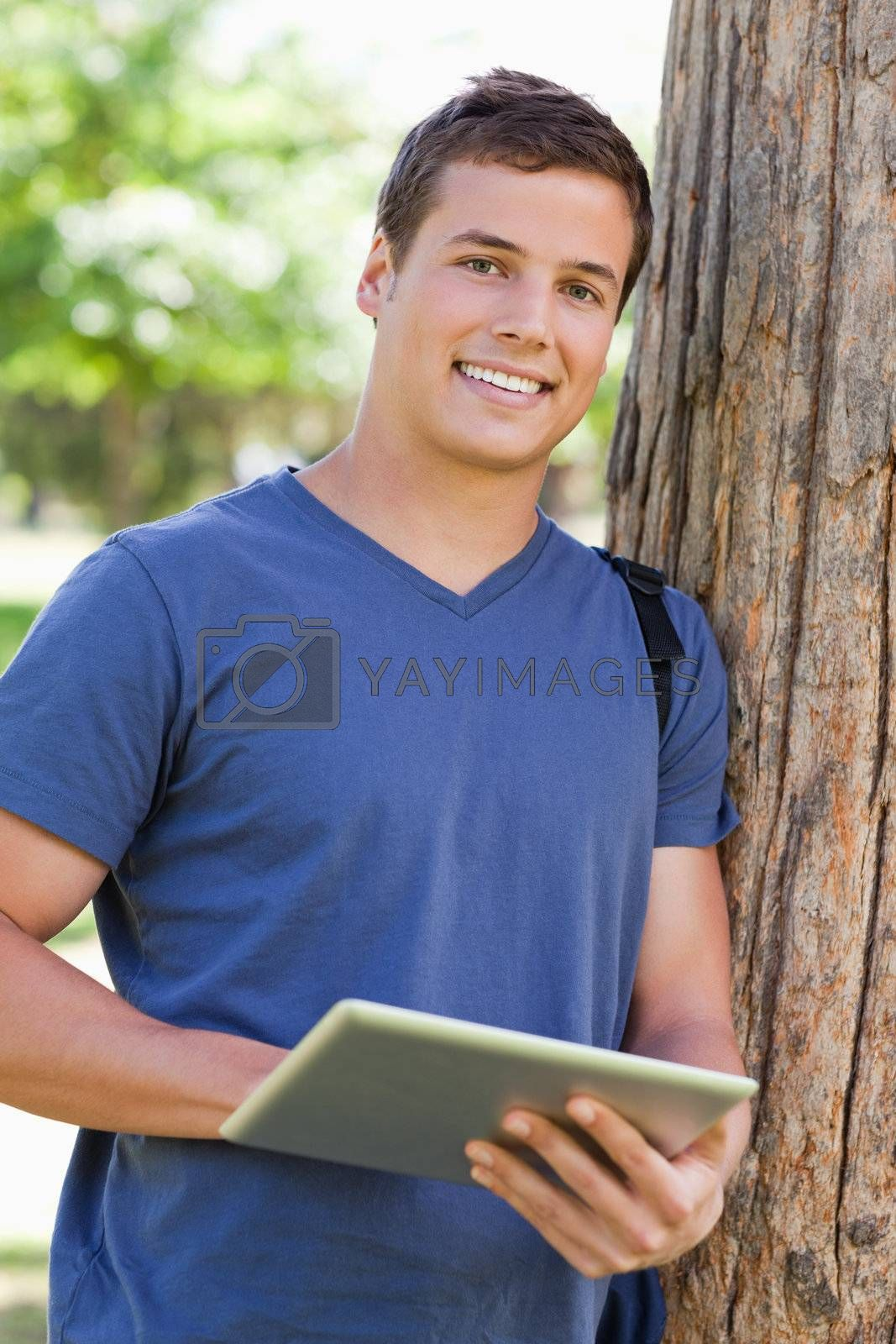 Close-up of a student leaning against a tree while using a touch pad in a park