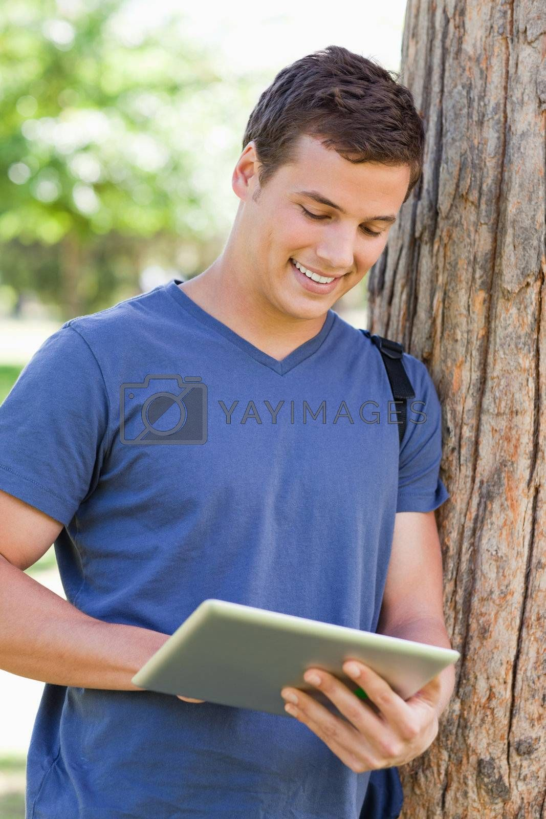 Close-up of a young man leaning against a tree while using a touch pad in a park