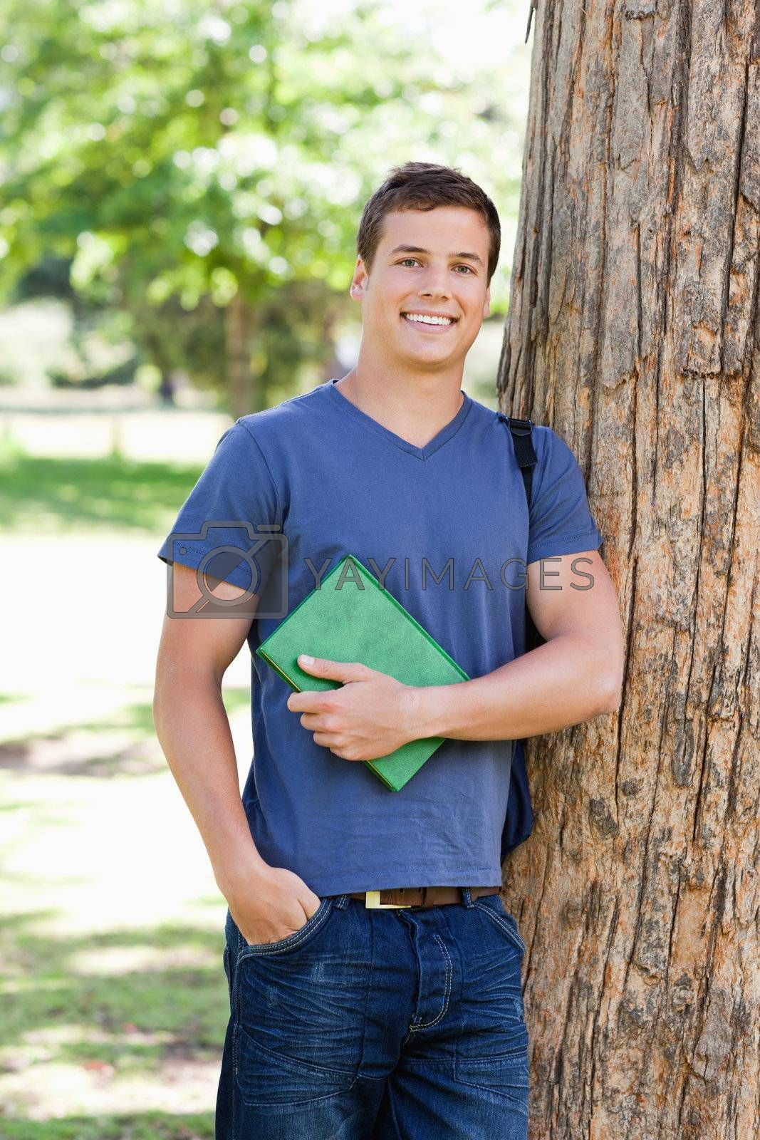 Portrait of a muscled student holding a textbook in a park