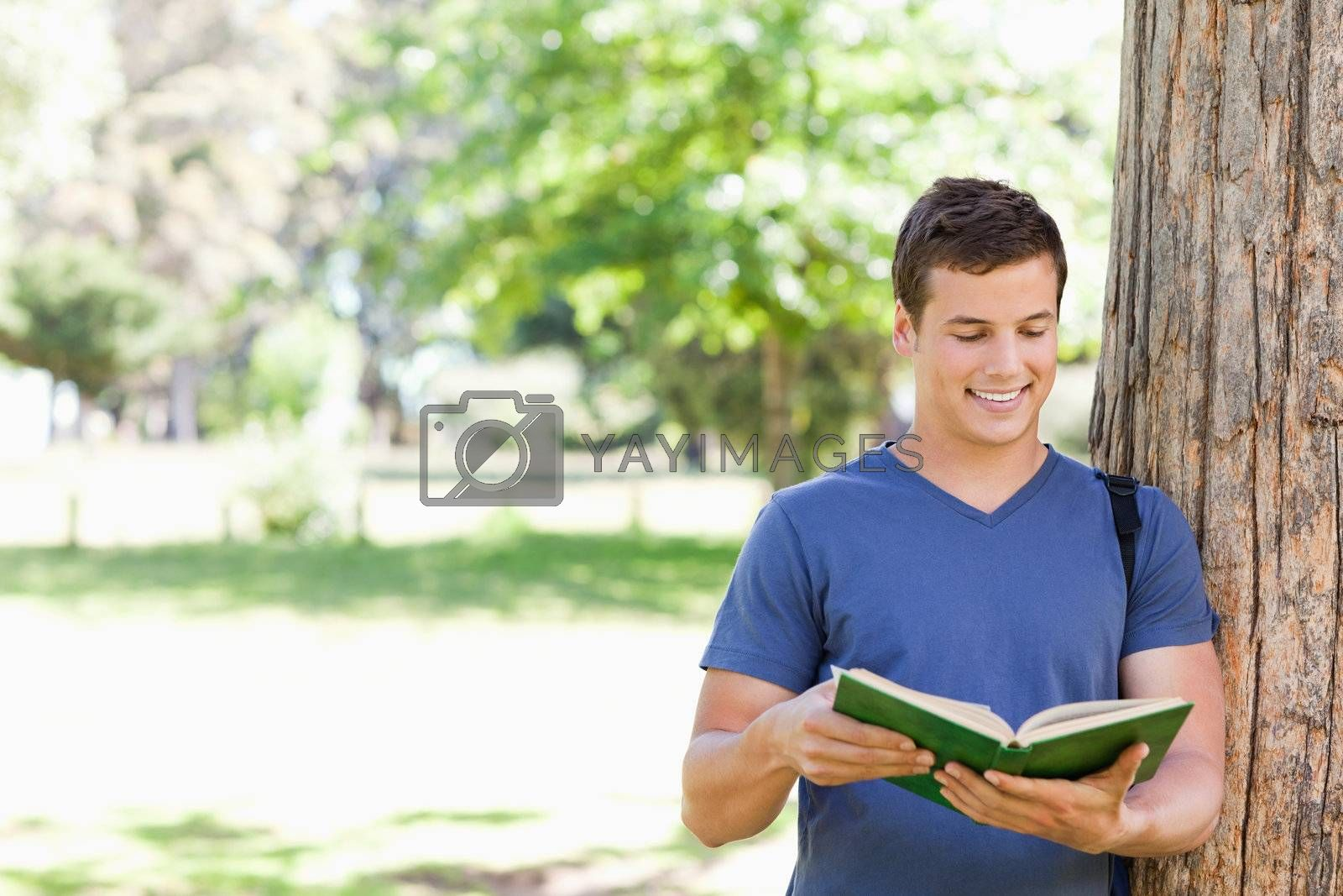 Muscled student holding a textbook in a park