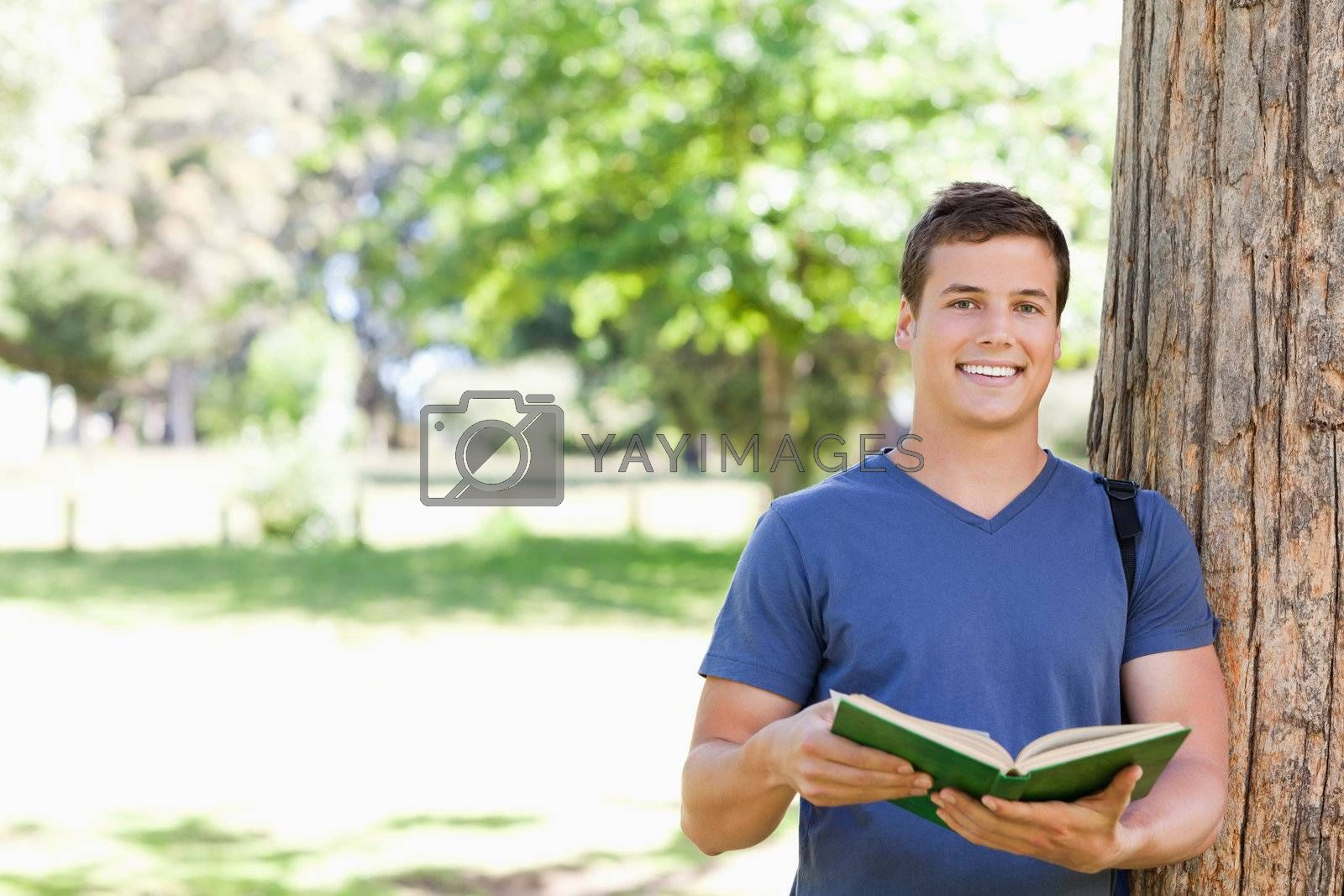 Portrait of a smiling toothy student holding a textbook in a park