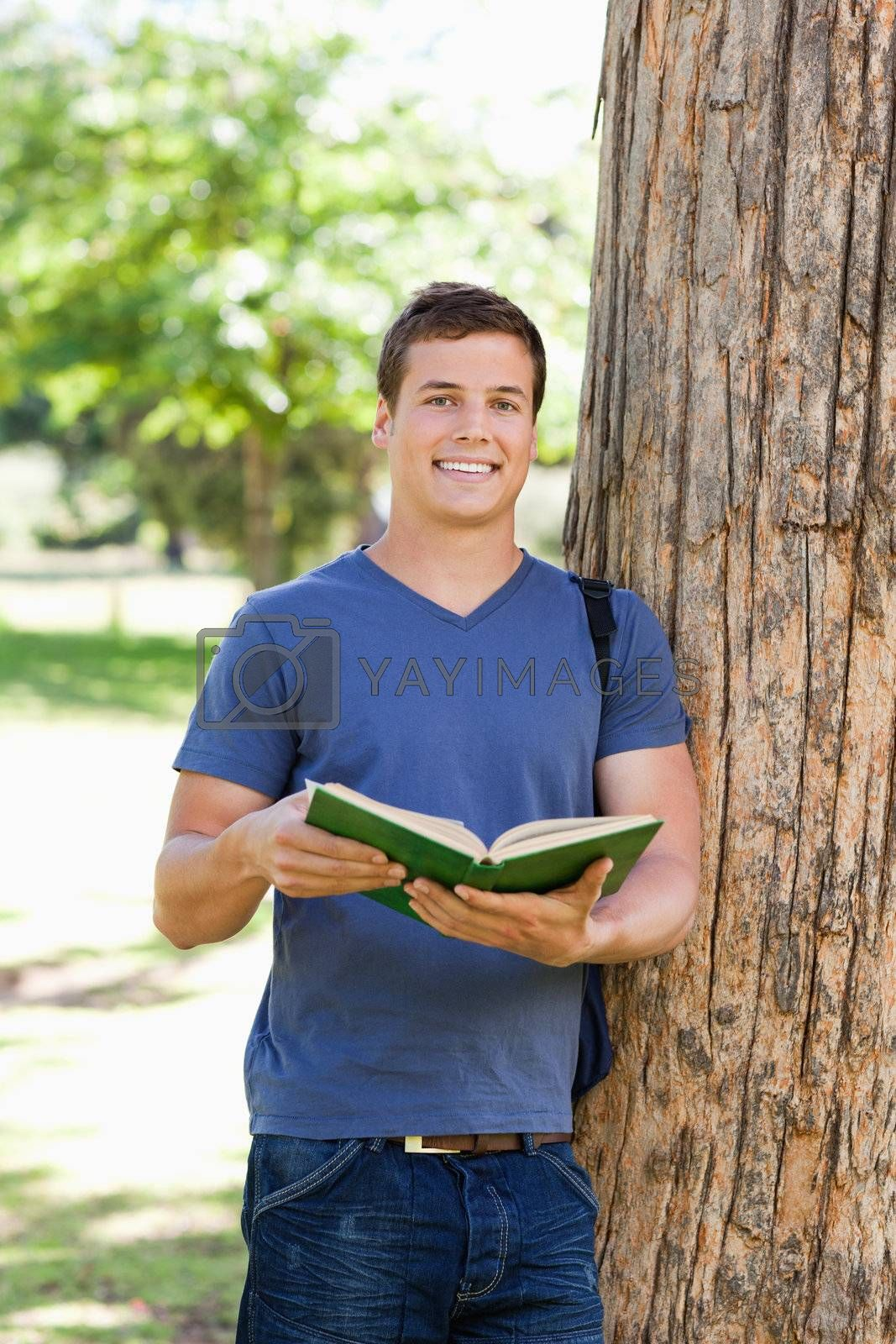 Portrait of a muscled young man holding a book in a park