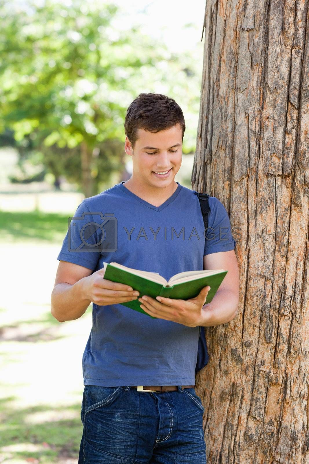 Muscled young man reading a book in a park