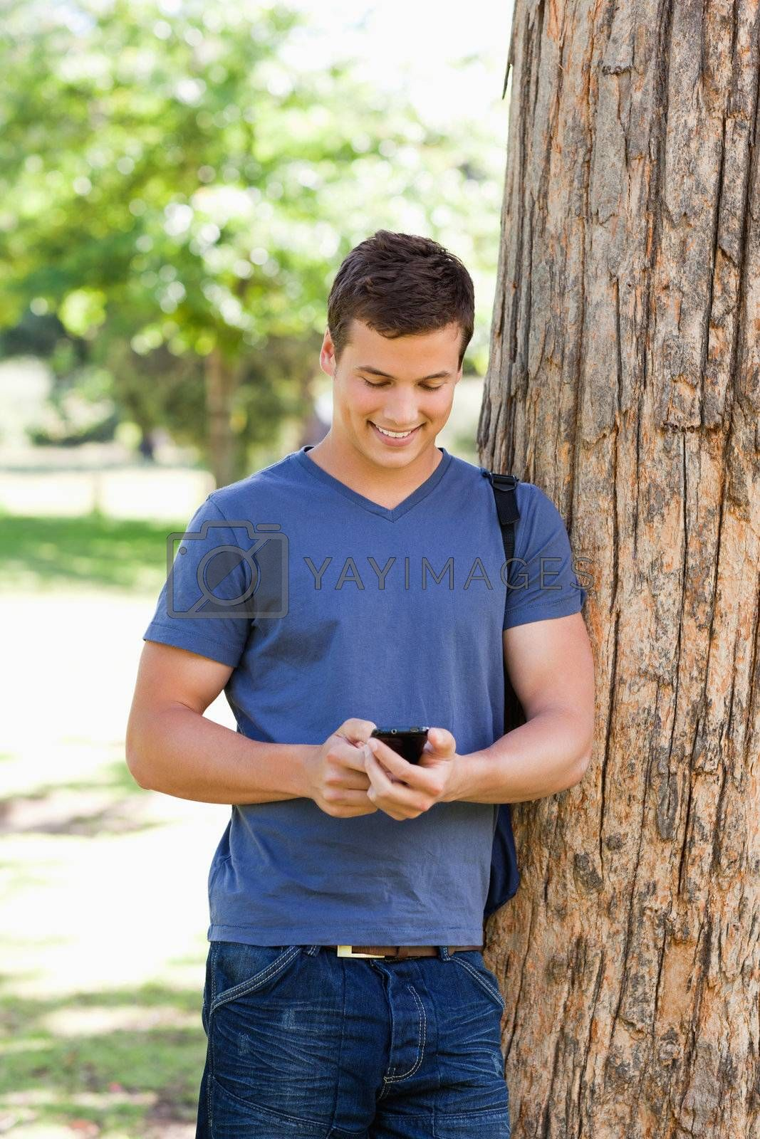Muscled young man using a smartphone in a park