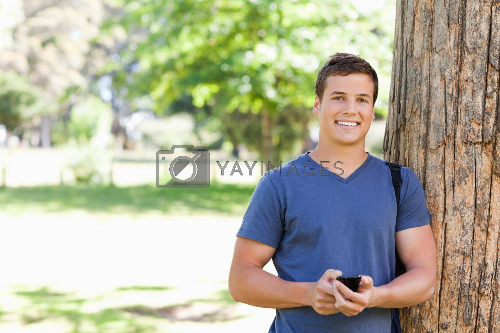 Portrait of a muscled young man with a smartphone in a park