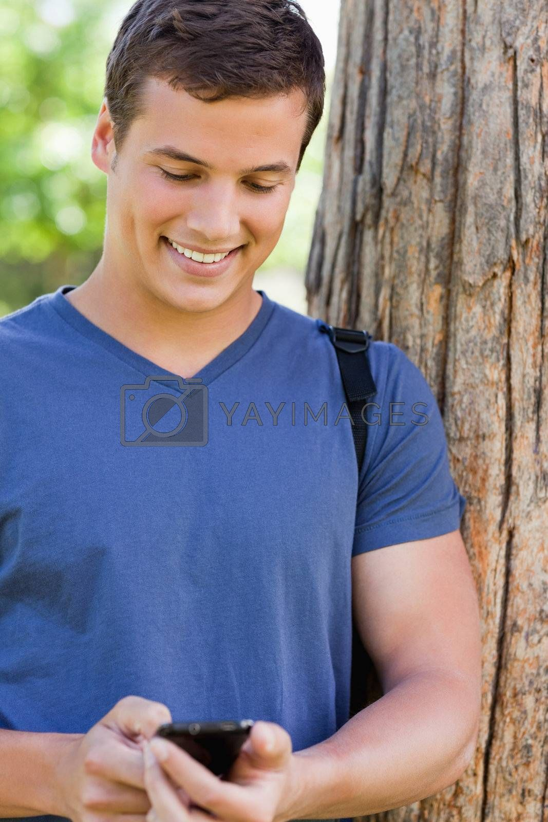 Close-up of a muscled young man using a smartphone in a park