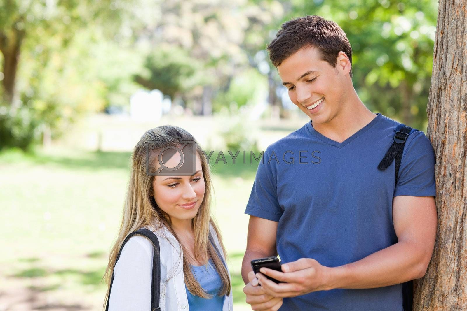 Close-up of a student showing his smartphone screen to a girl in a park