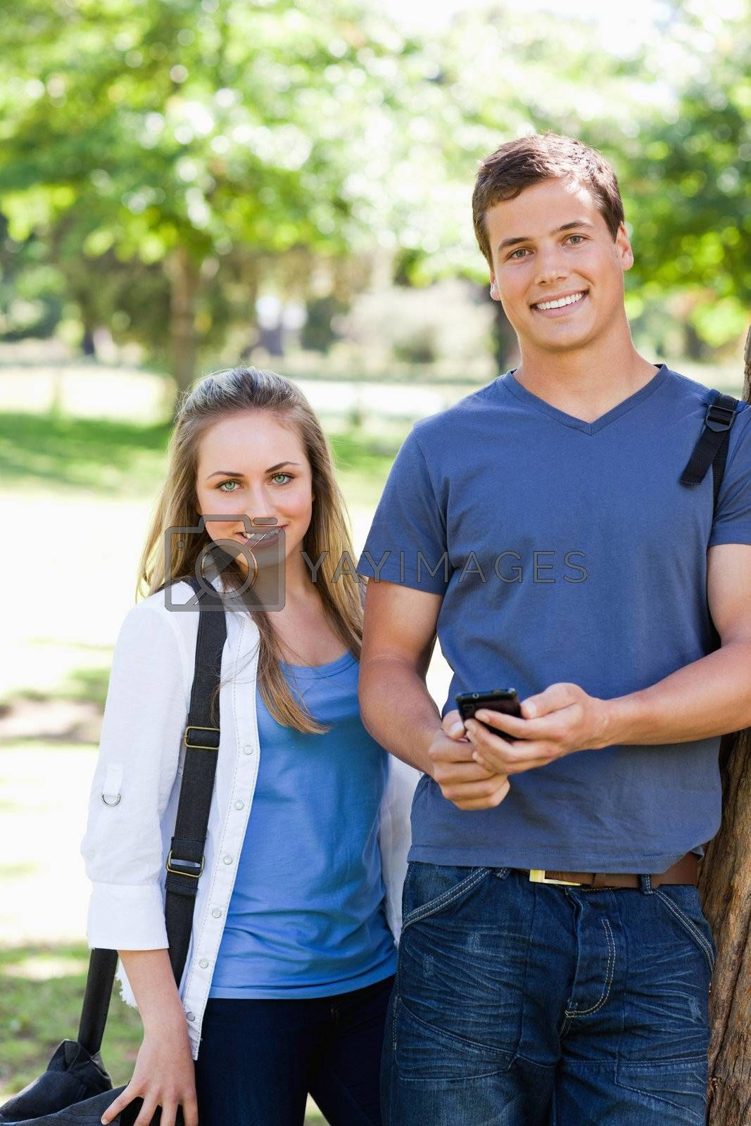 Portrait of two students with a smartphone in a park