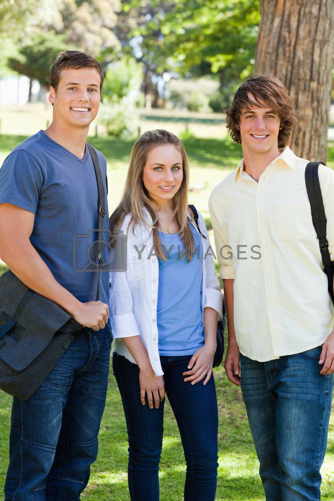 Smiling students with their bags posing in a park