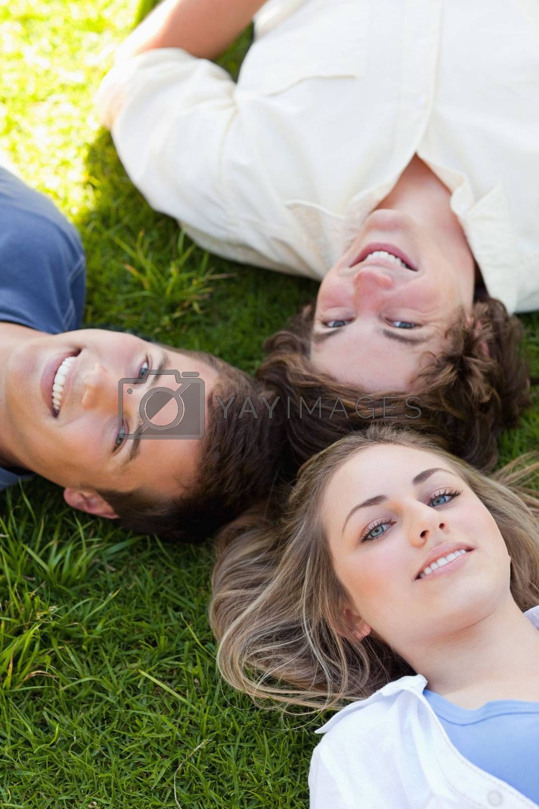 Three students resting together while looking at camera in the grass