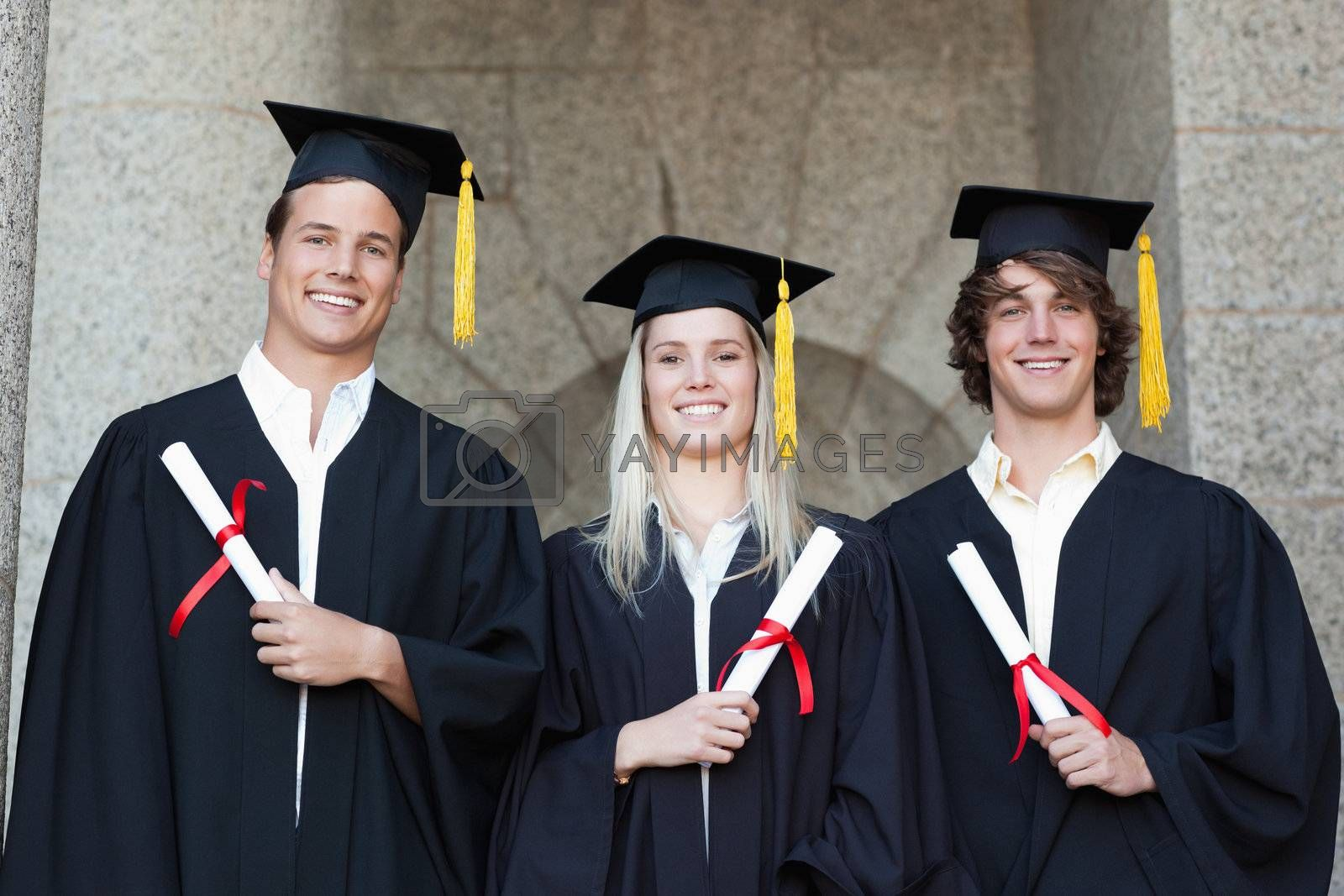Graduates holding their diploma while posing with university in backgroung