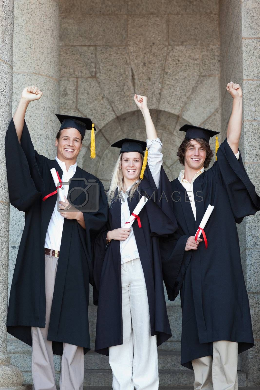 Happy graduates raising arm with university in backgroung