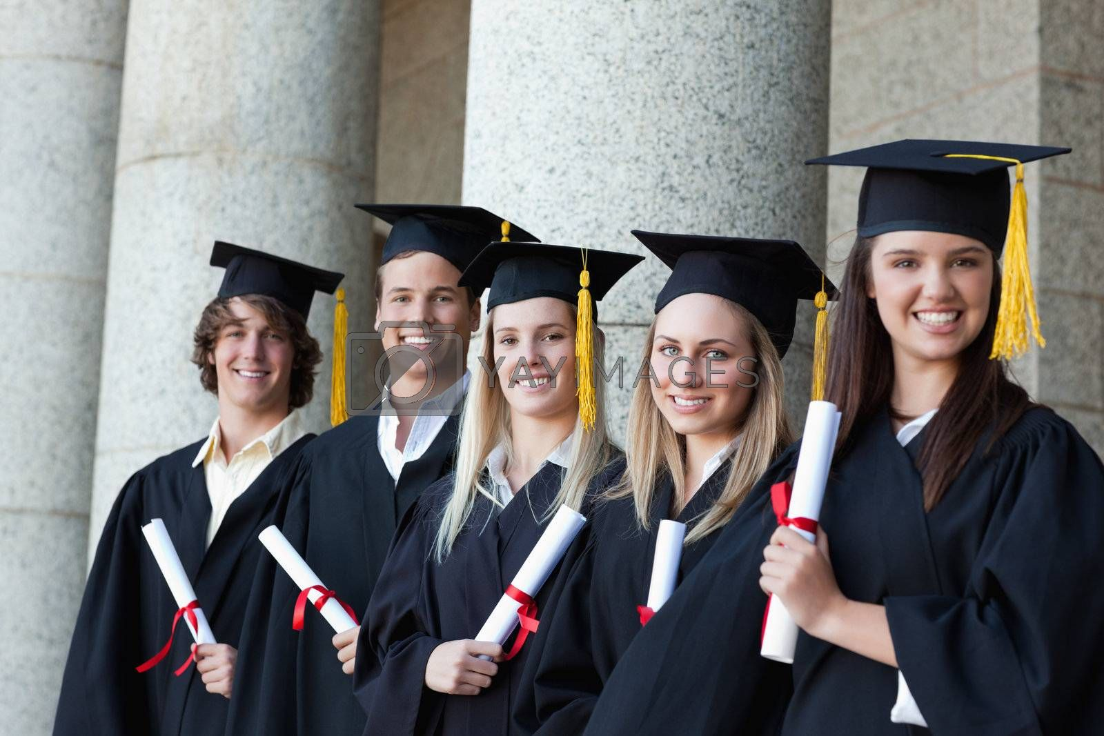 Smiling graduates posing in single line with columns in background
