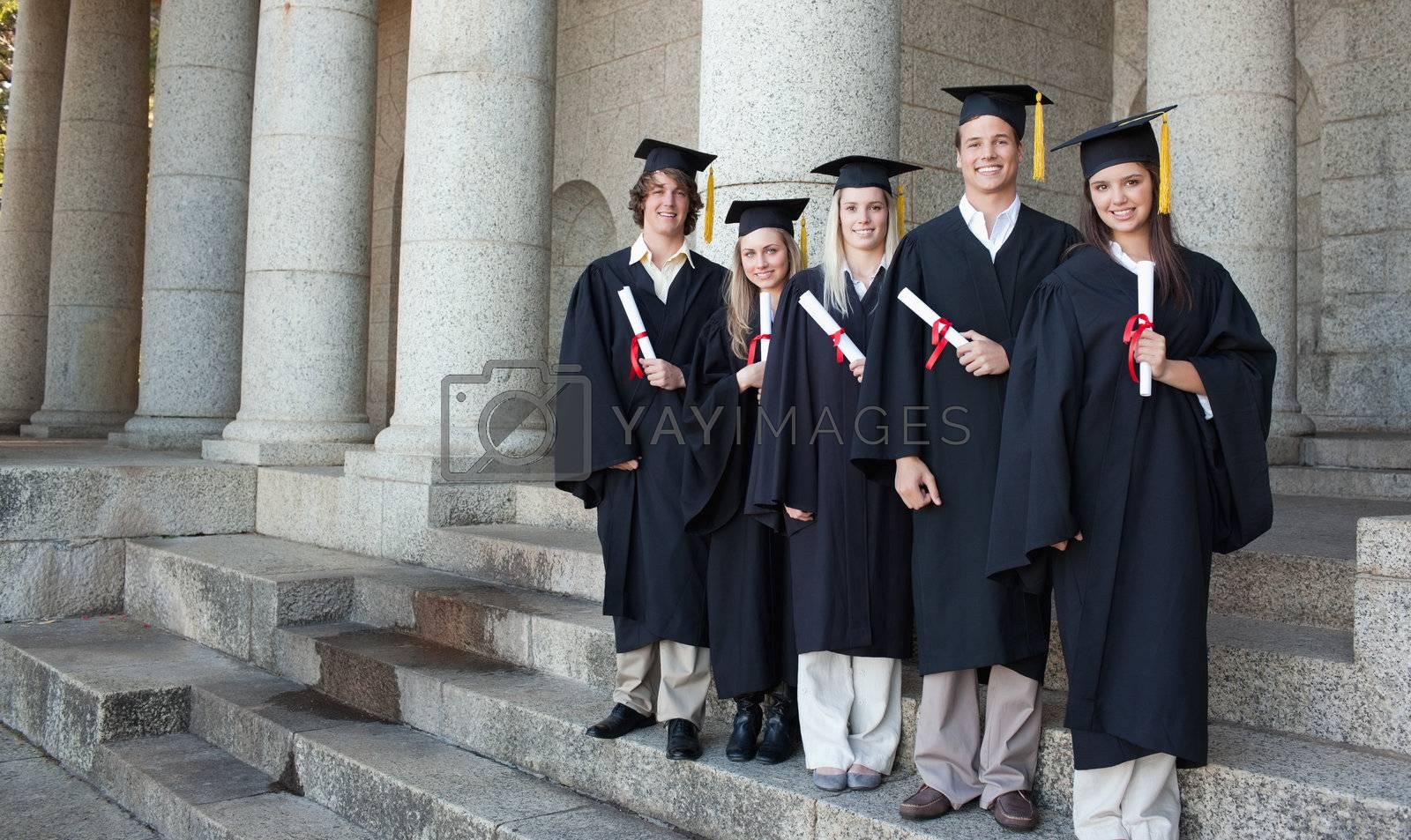 Five happy graduates posing in front of the university