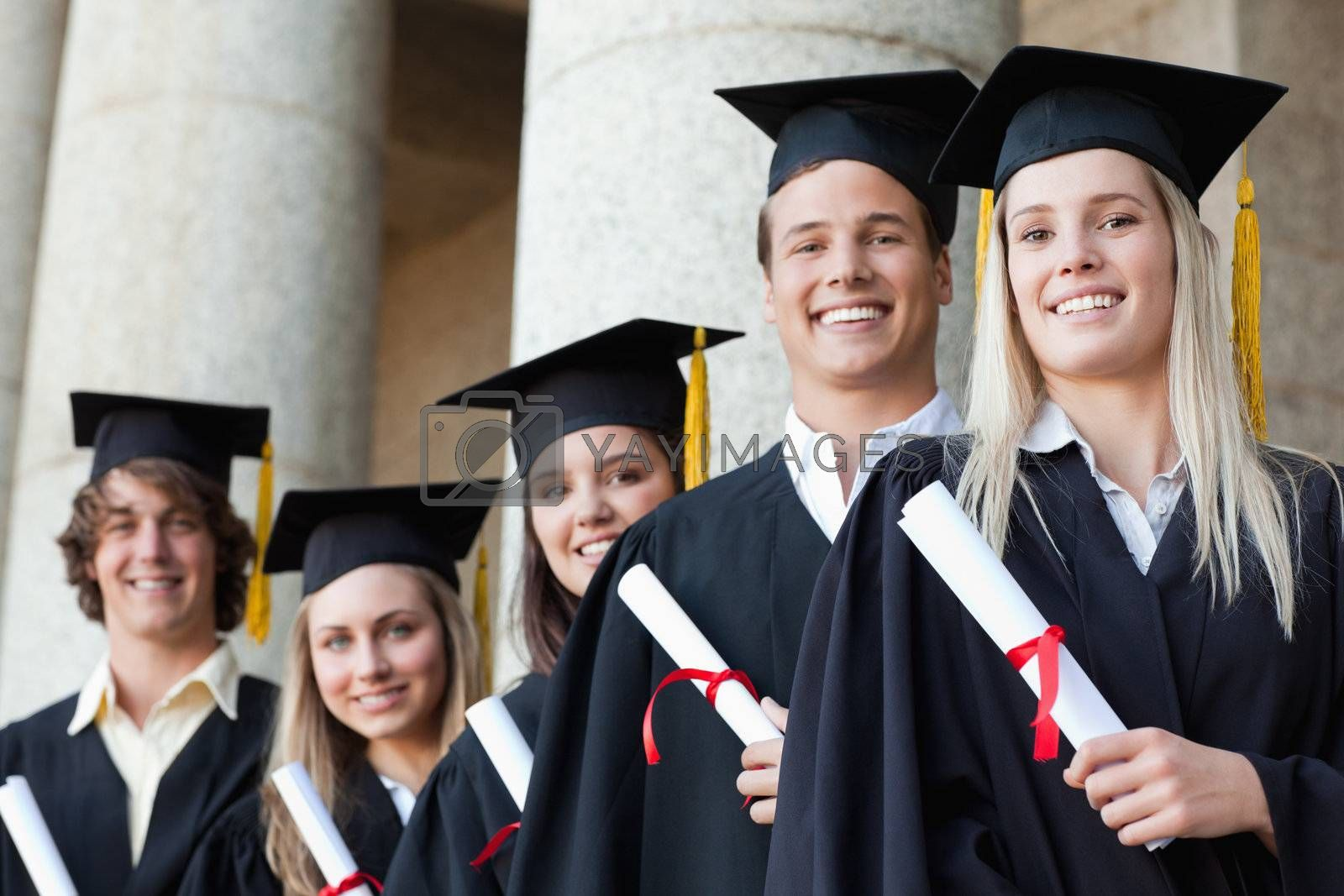 Close-up of five smiling graduates posing in front of the university
