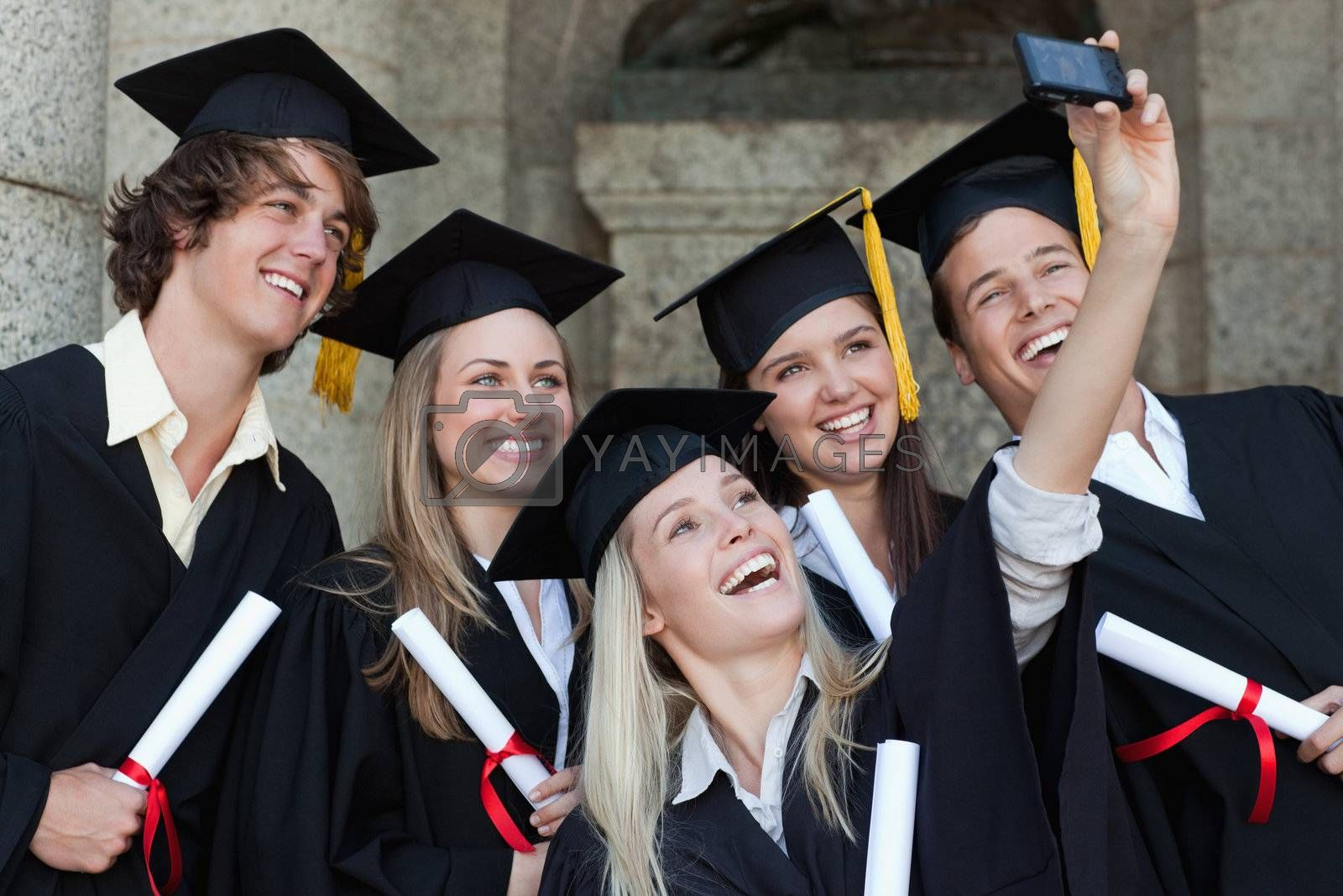Close-up of happy graduates taking a picture of themselves in front of the university