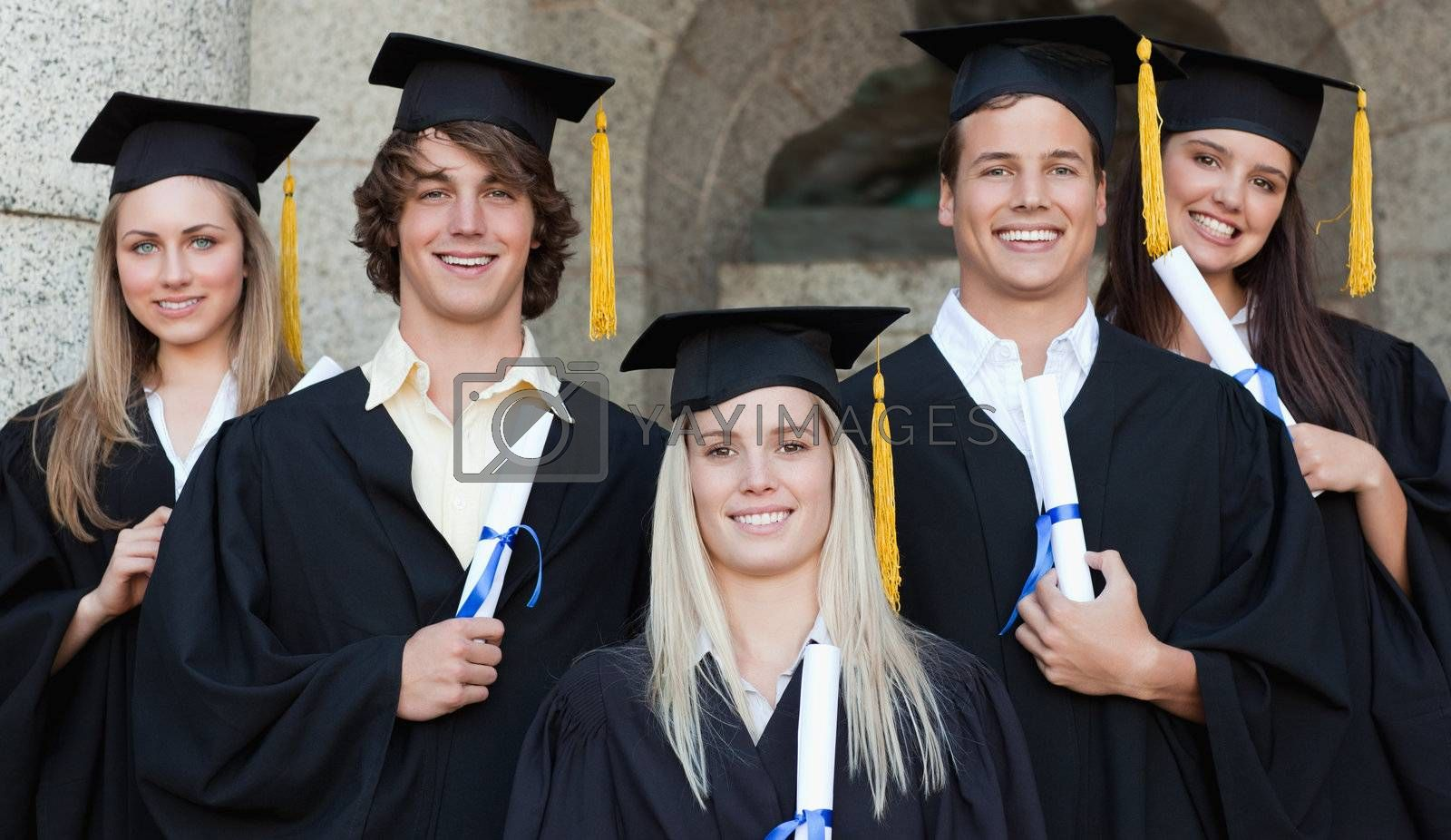 Close-up of five happy graduates posing in front of the university