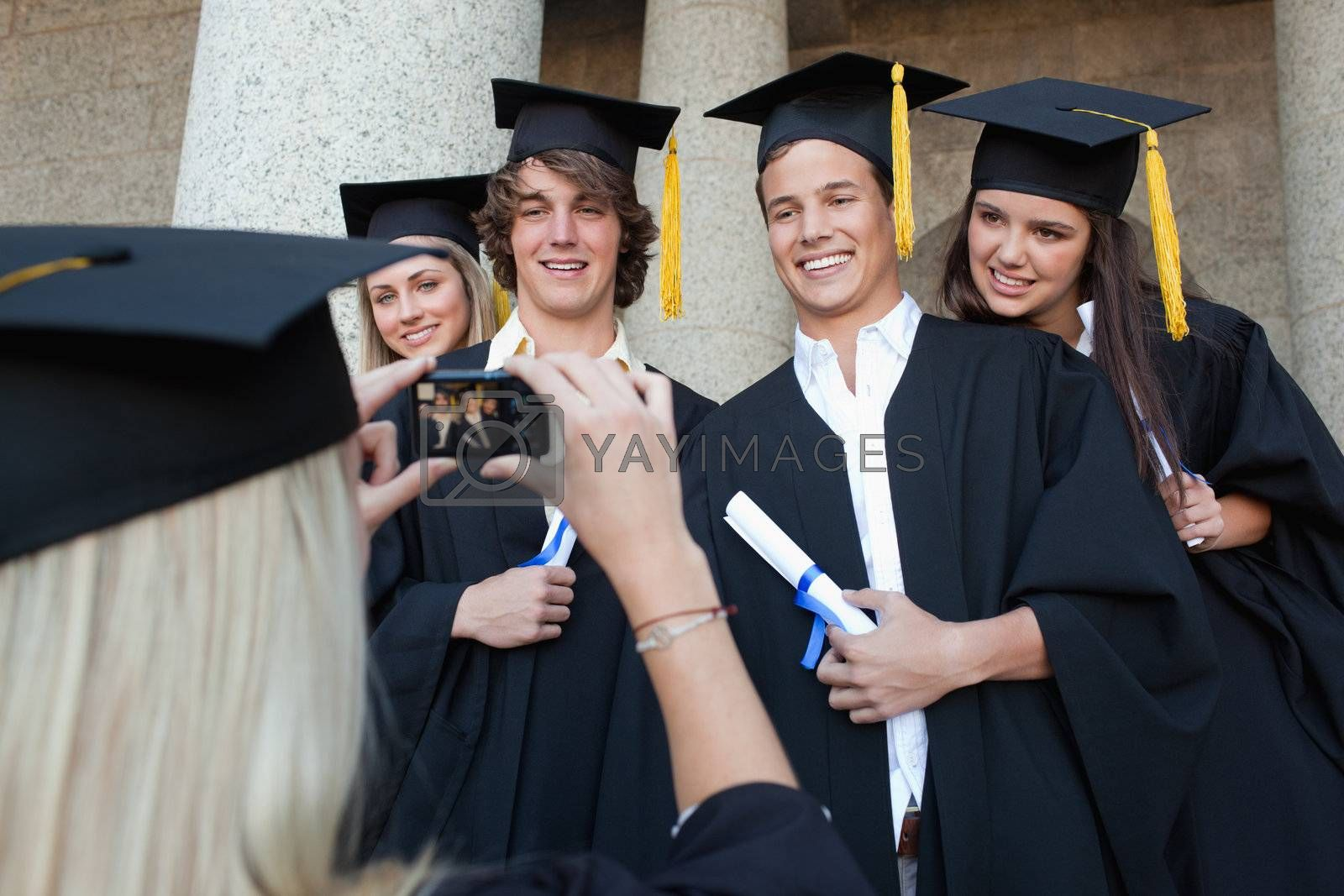 Close-up of a blonde graduate taking a picture of her friend in front of the university