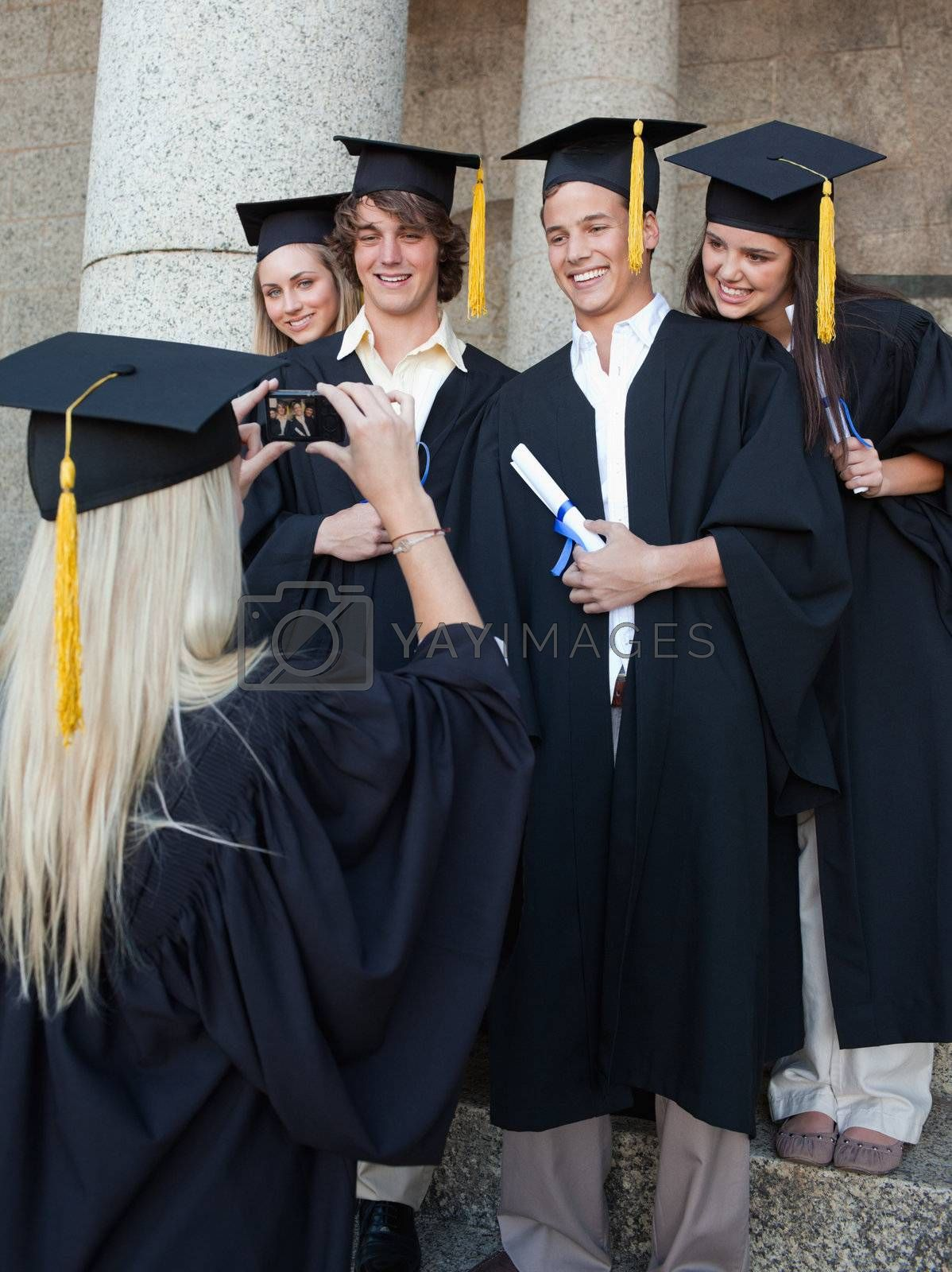 Blonde graduate taking a picture of her friend in front of the university