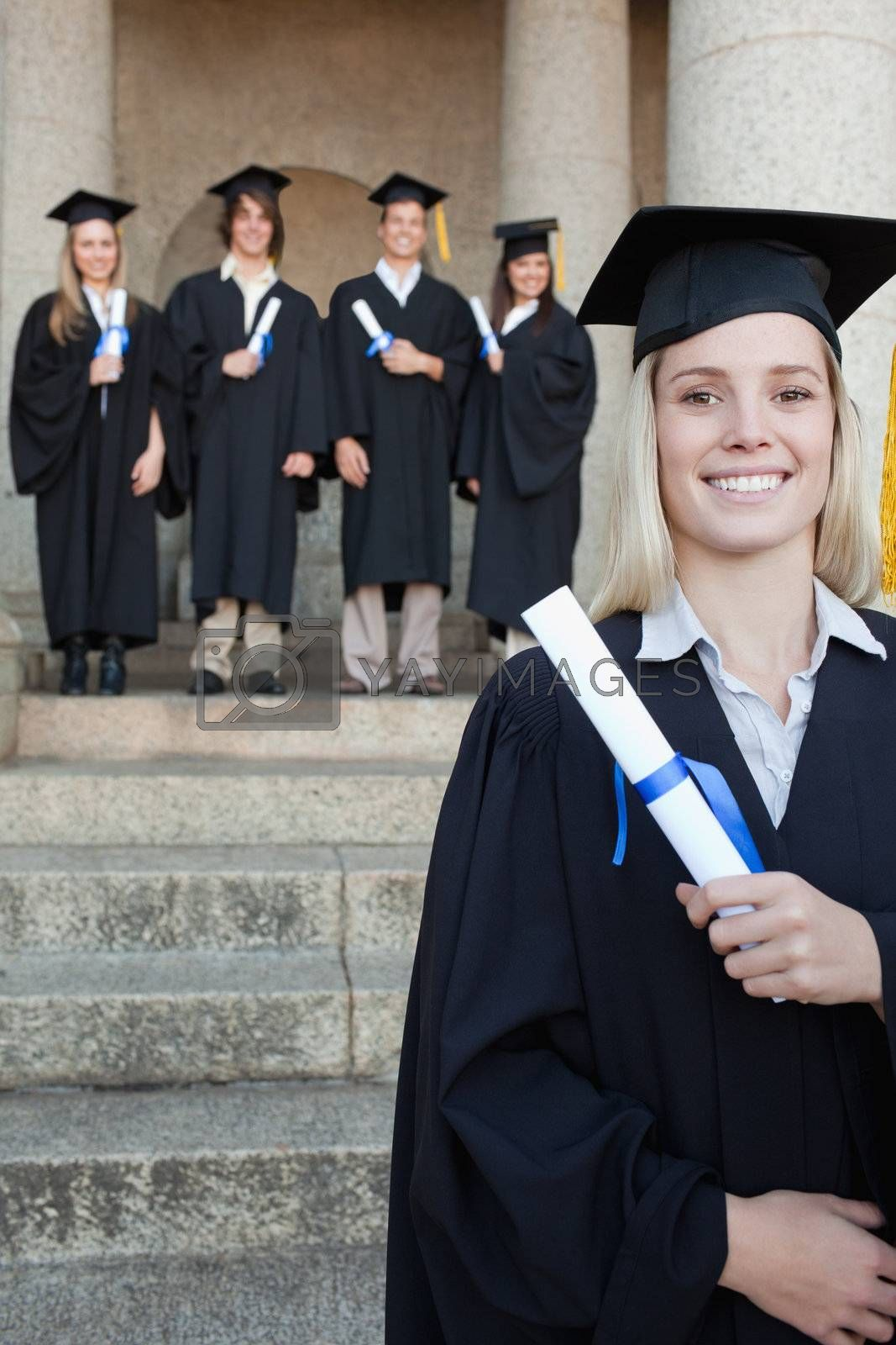 Close-up of a blonde graduate smiling with her friends in background in front of the university