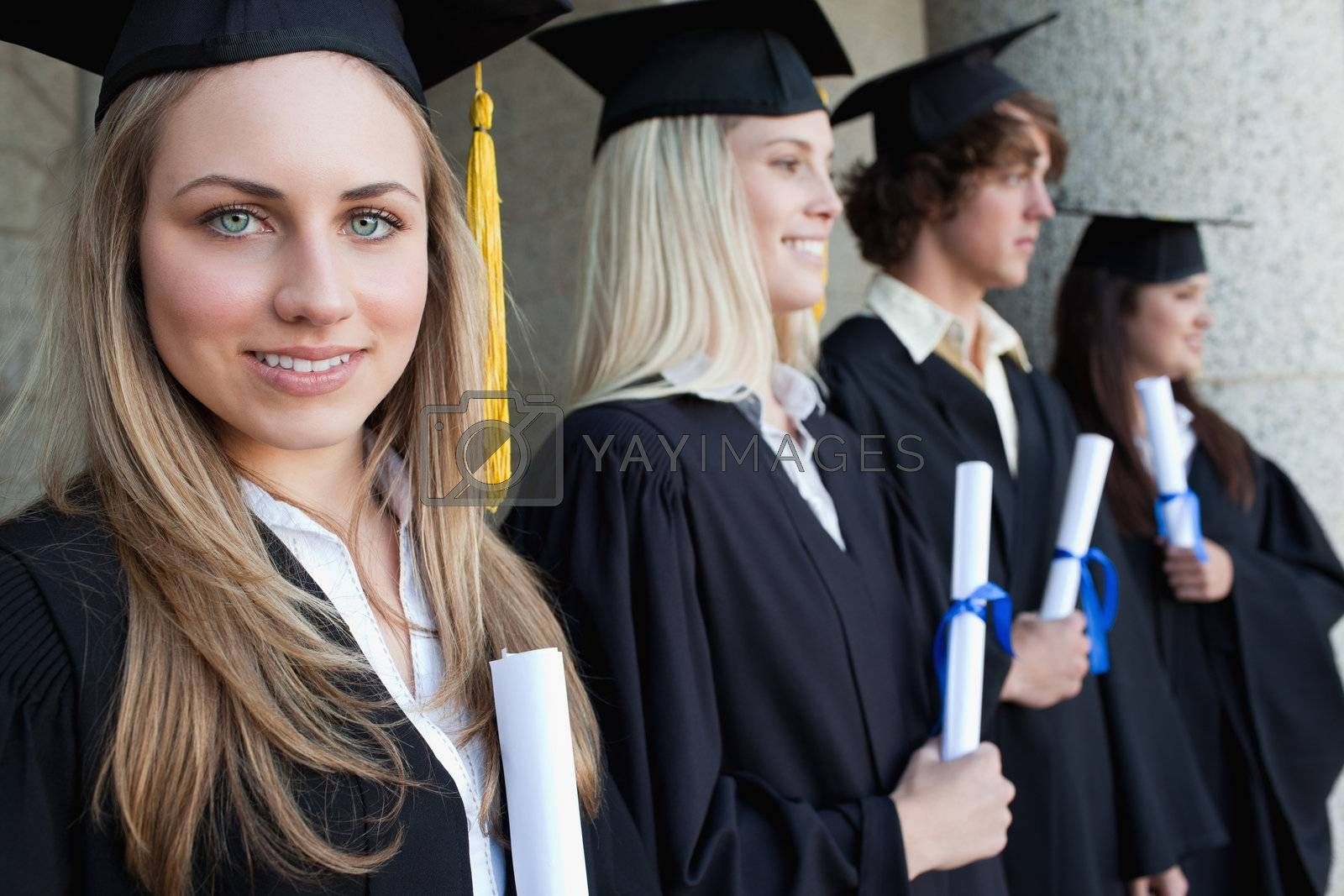 Close-up of a blonde graduate with blue eyes next to her friends posing