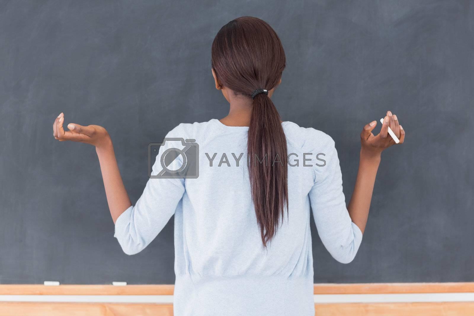 Black woman in front of a blackboard in a classroom