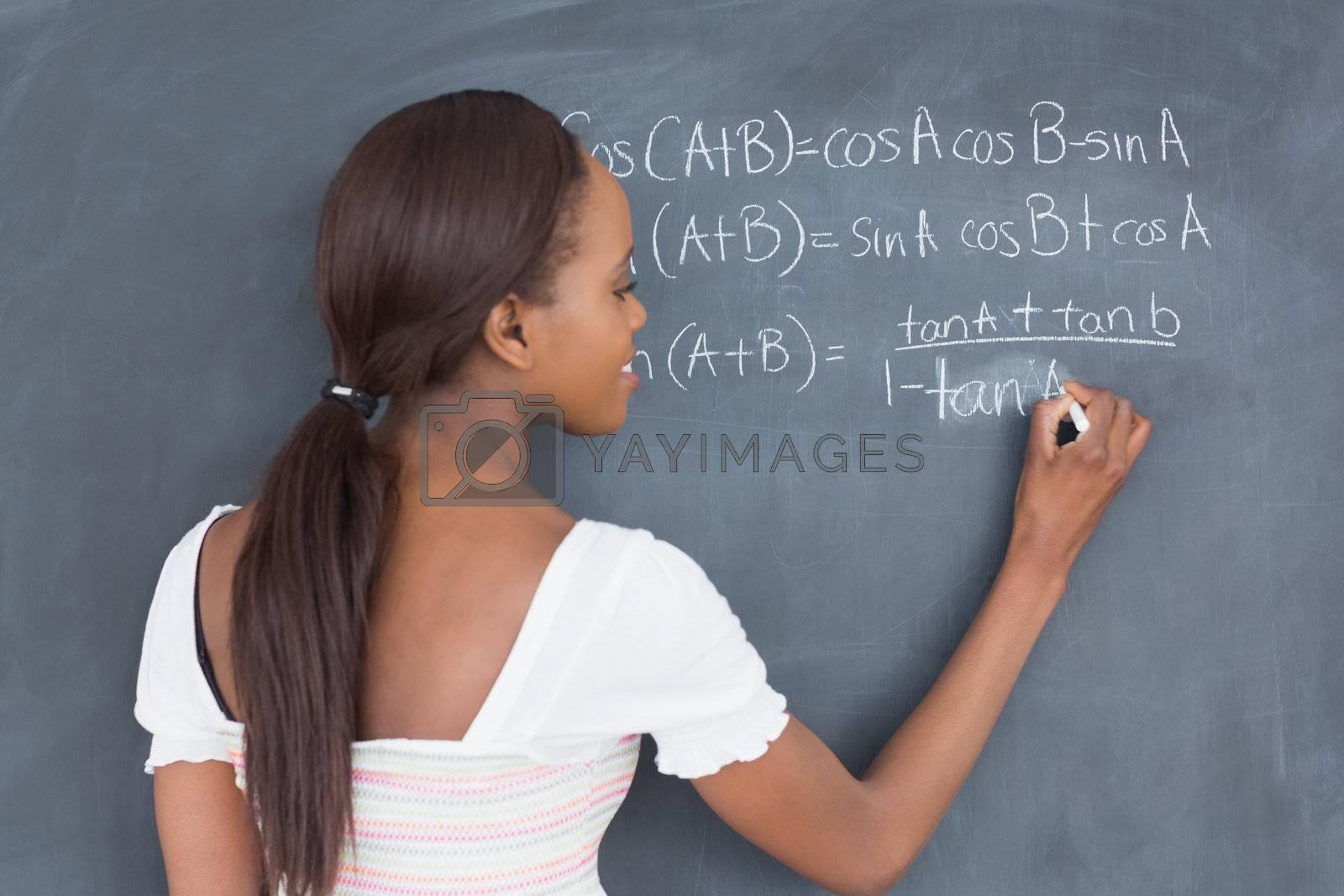Black student writing on a blackboard in a classroom