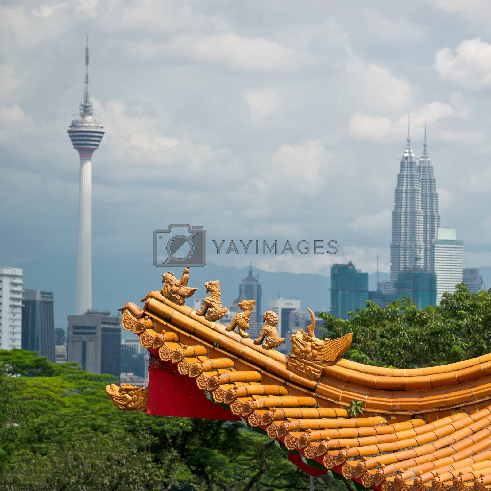 Mixture of architectural styles in Kuala Lumpur, Malaysia.  The roof of ancient chinese temple on the background of two symbols of Kuala Lumpur - KL Tower and Petronas Twin Towers.