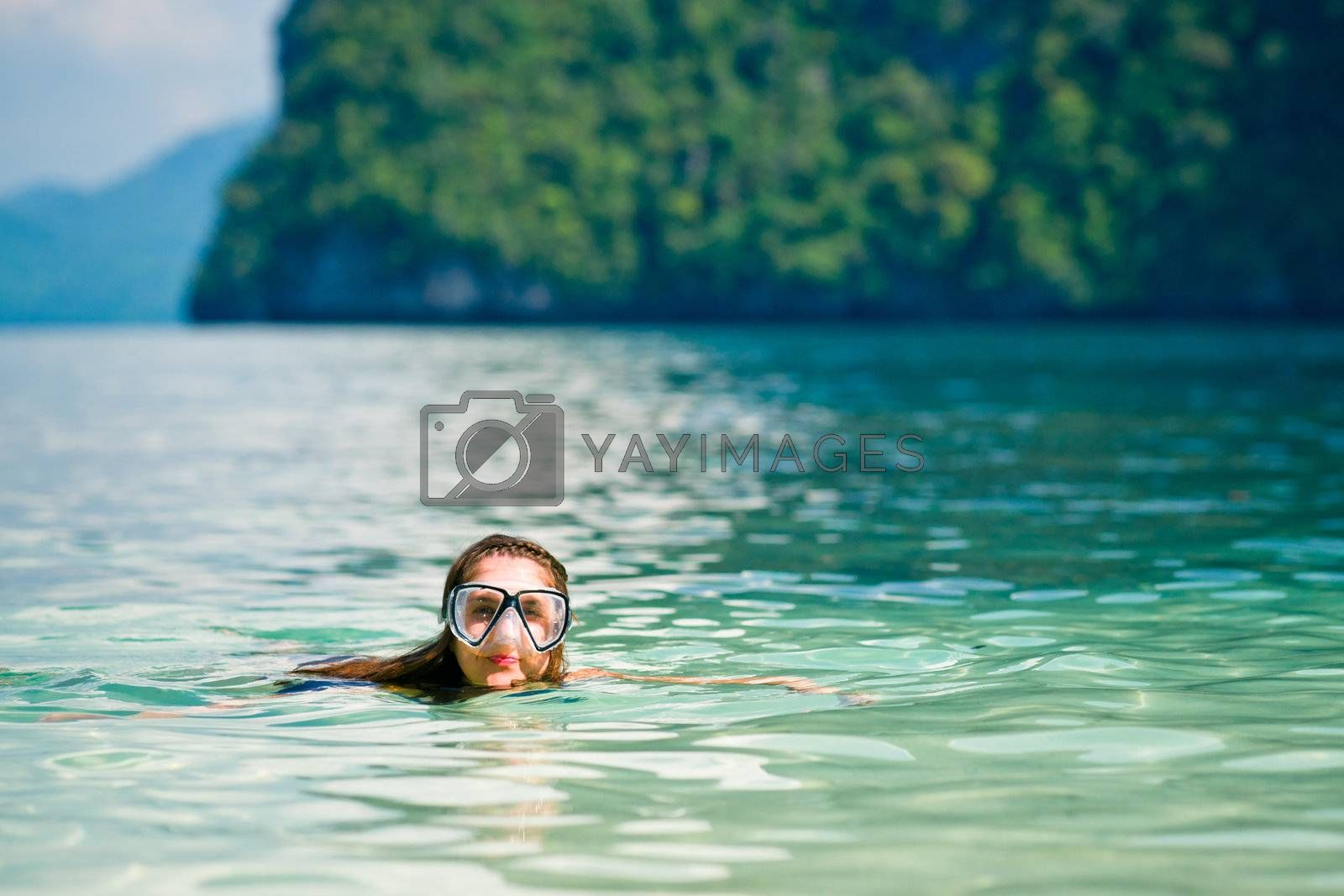 Woman with mask swimming in the sea