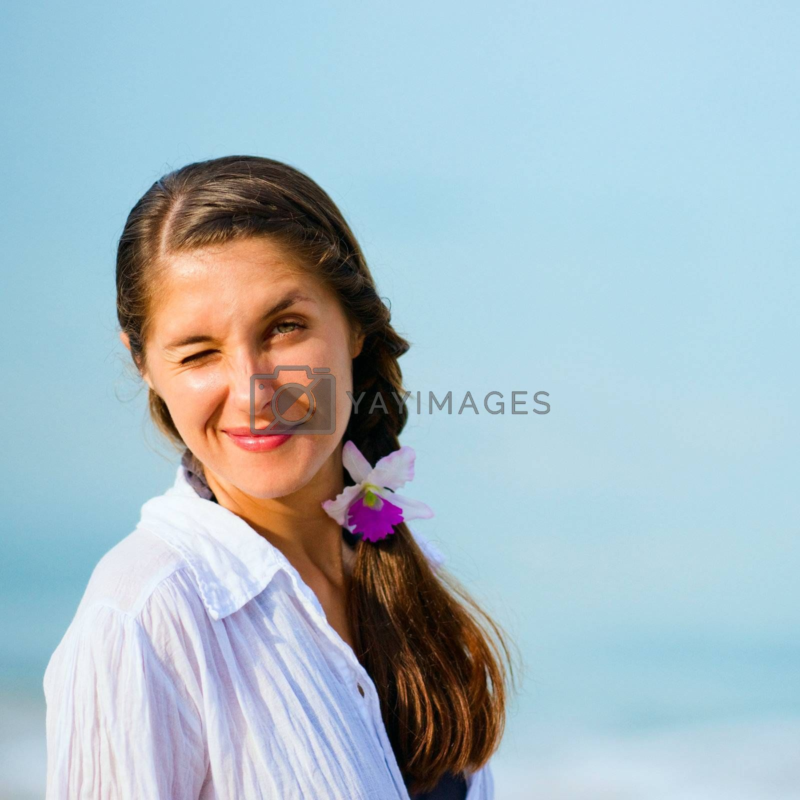 Portrait of young winking woman on the sky background