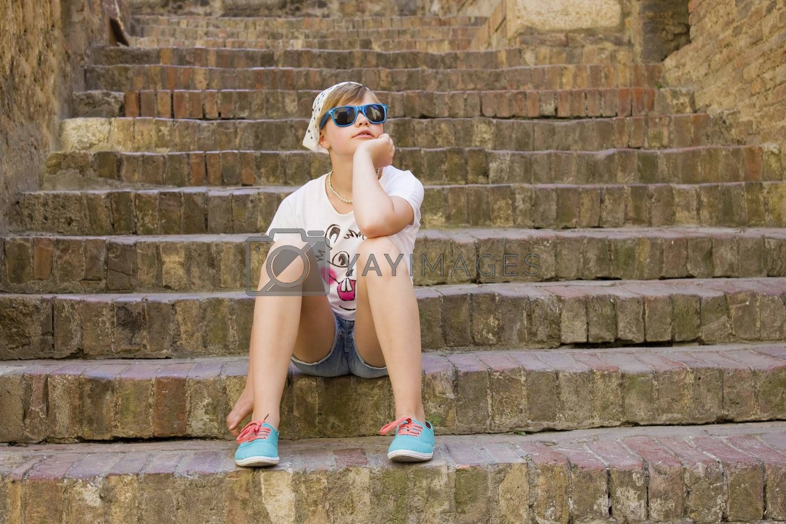 young girl sitting on old stone stairs, Gimignano, Tuscany