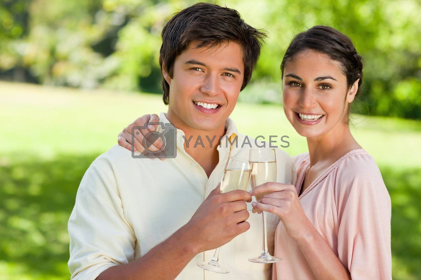 Man and a woman smiling while they touch glasses of champagne in celebration