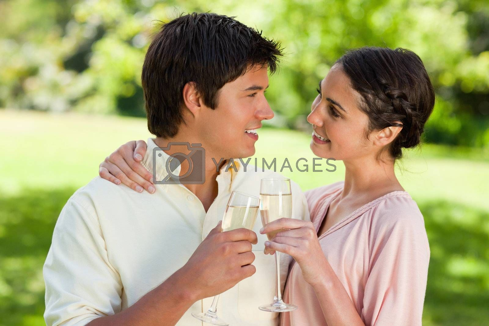 Man and a woman smiling happily as they look at each other while touching glasses of champagne in celebration