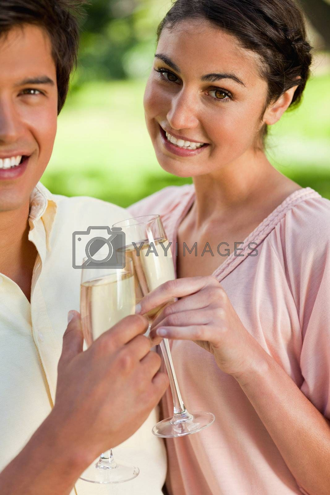 Woman smiling joyfully while touching glasses of champagne with her friend in celebration