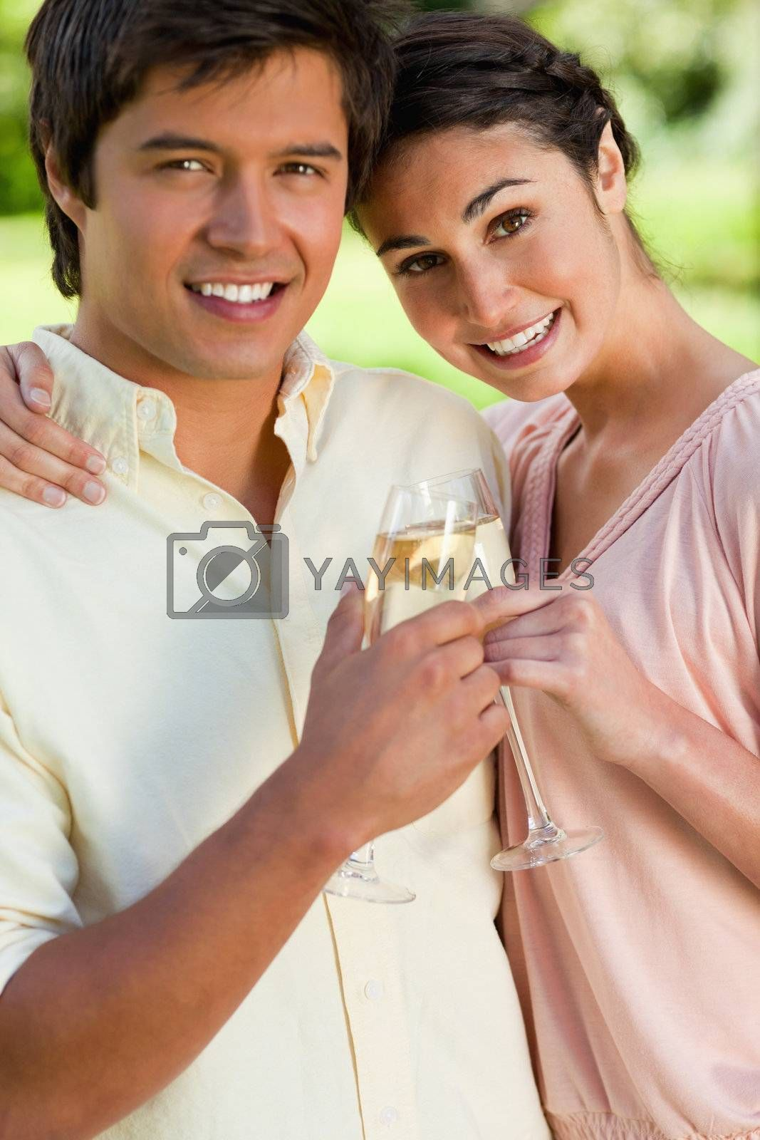 Woman smiling and leaning against her smiling friend while touching glasses of champagne in celebration