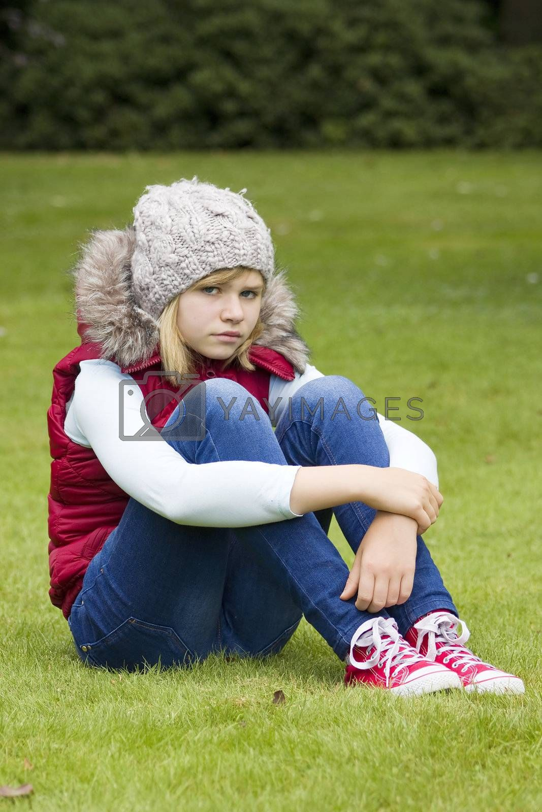young girl sitting on the grass in the park