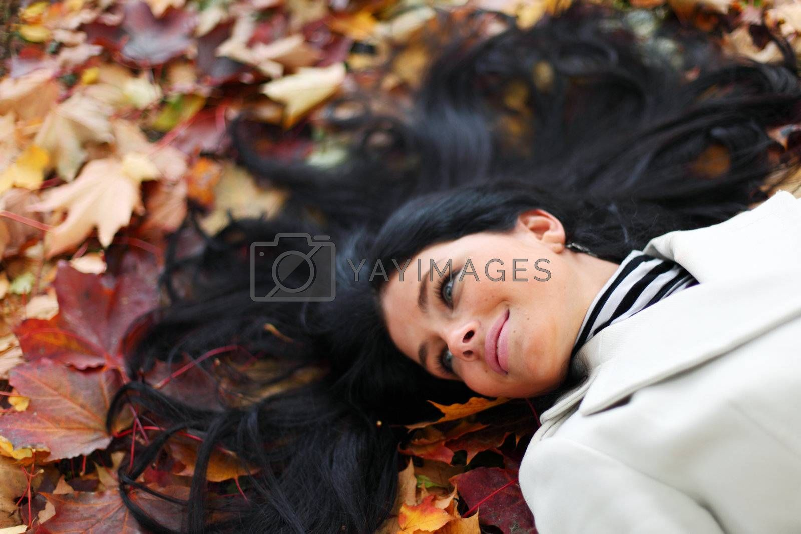 woman lay on yellow autumn leaves