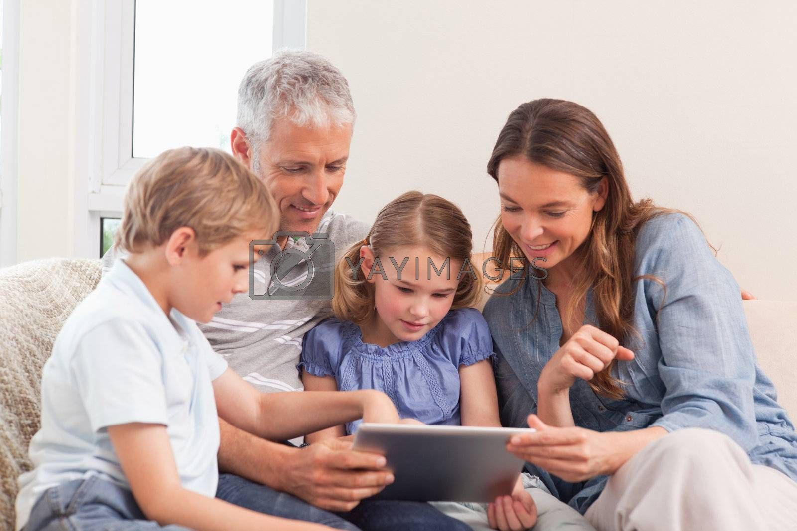 Happy family using a tablet computer in a living room