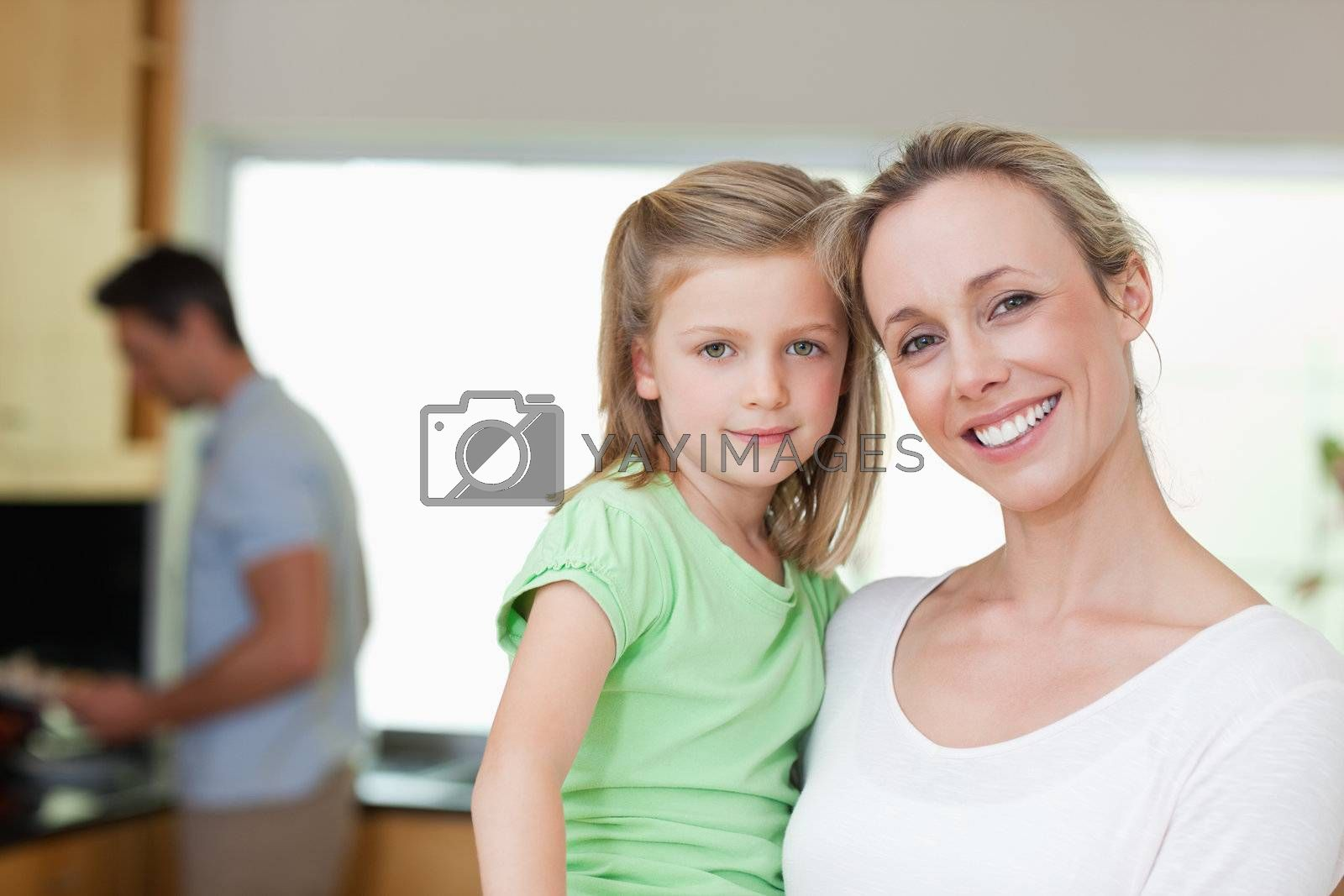 Mother and daughter with father in the background by Wavebreakmedia