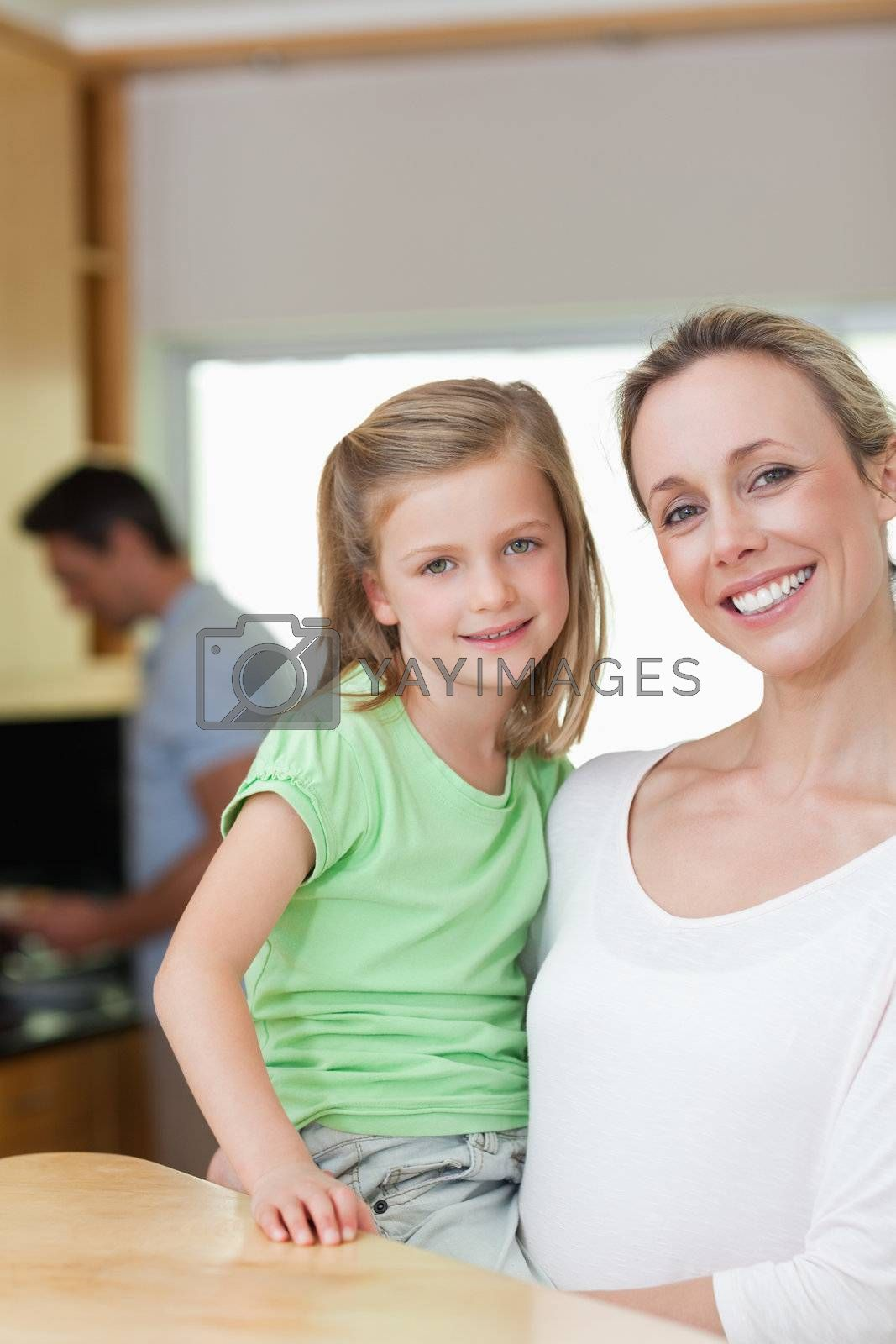 Mother holding her daughter with father in the background by Wavebreakmedia